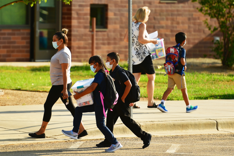 Parents and students wearing masks walk to school.