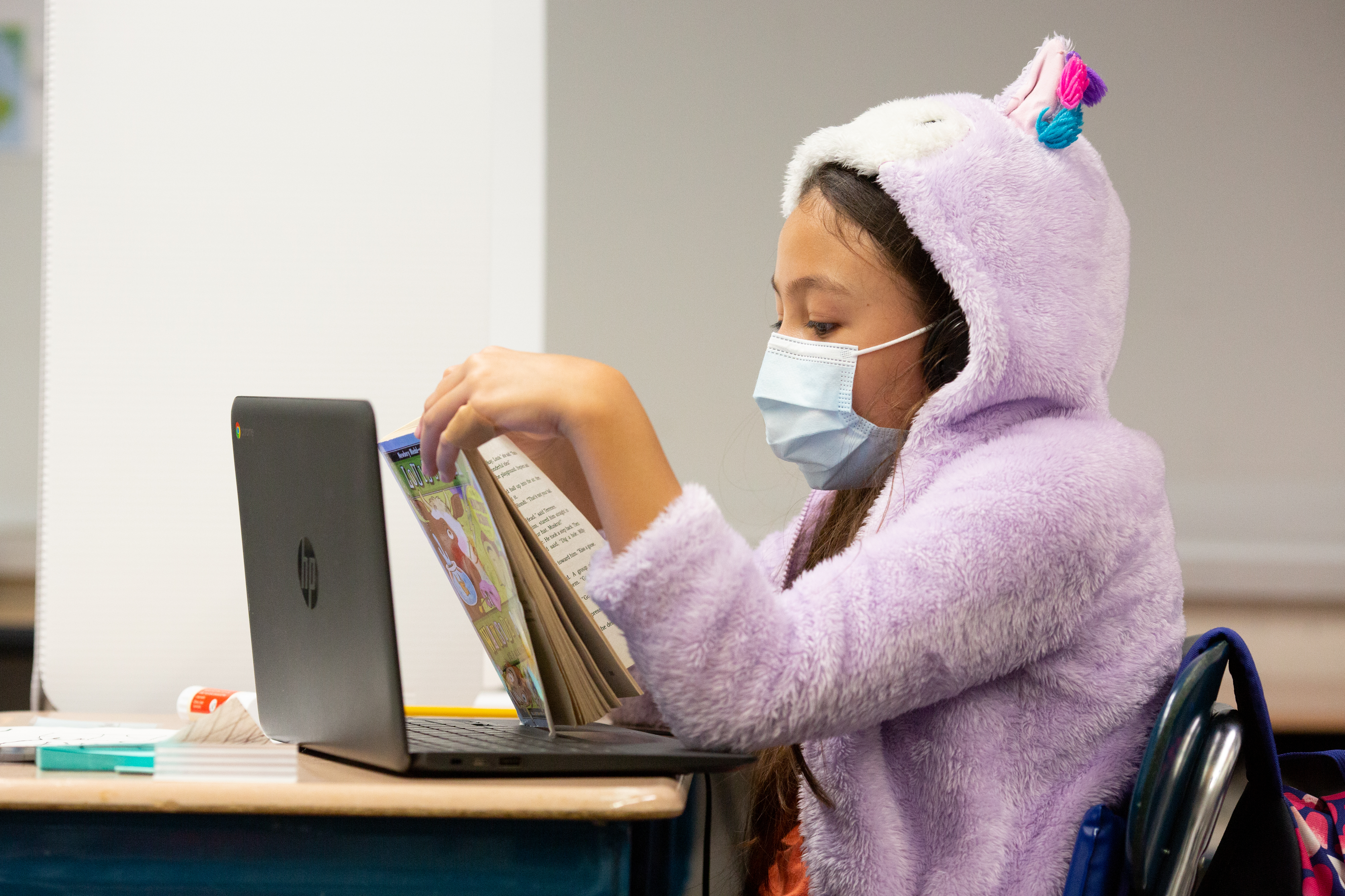 Student wearing a mask and lavender hooded sweatshirt with ears is reading a book in class.