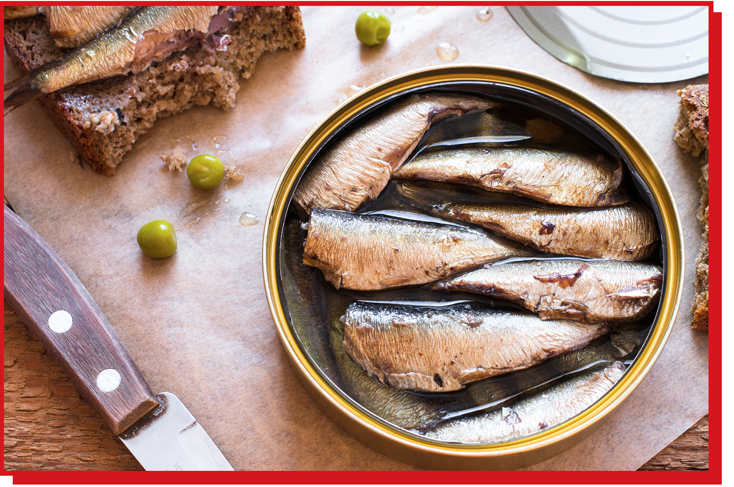 An open can of sardines with the filets still in their oil.