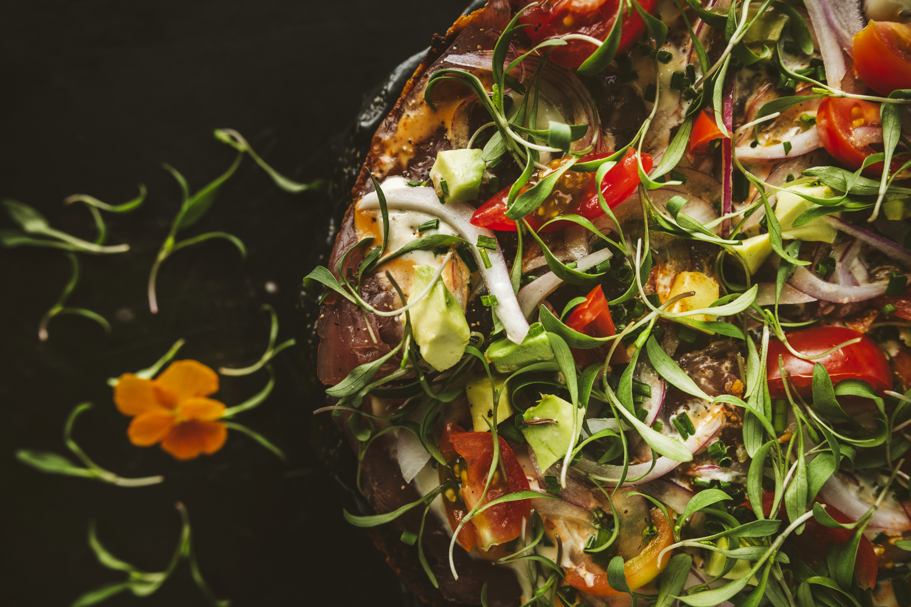 Pizza on a black background with tomatoes, micro greens, and peppers