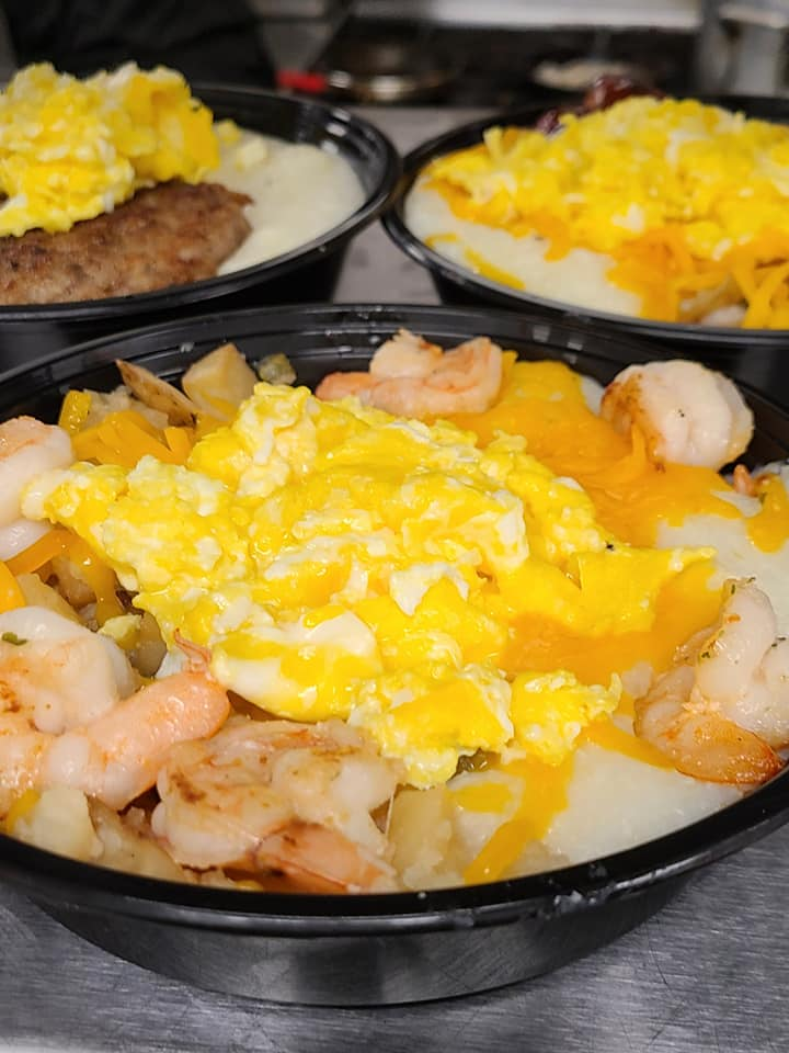 A bowl of shrimp, grits, and eggs