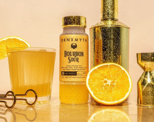 Drnxmyth's bourbon sour cocktail in a bottle with an orange half and gold shakers.