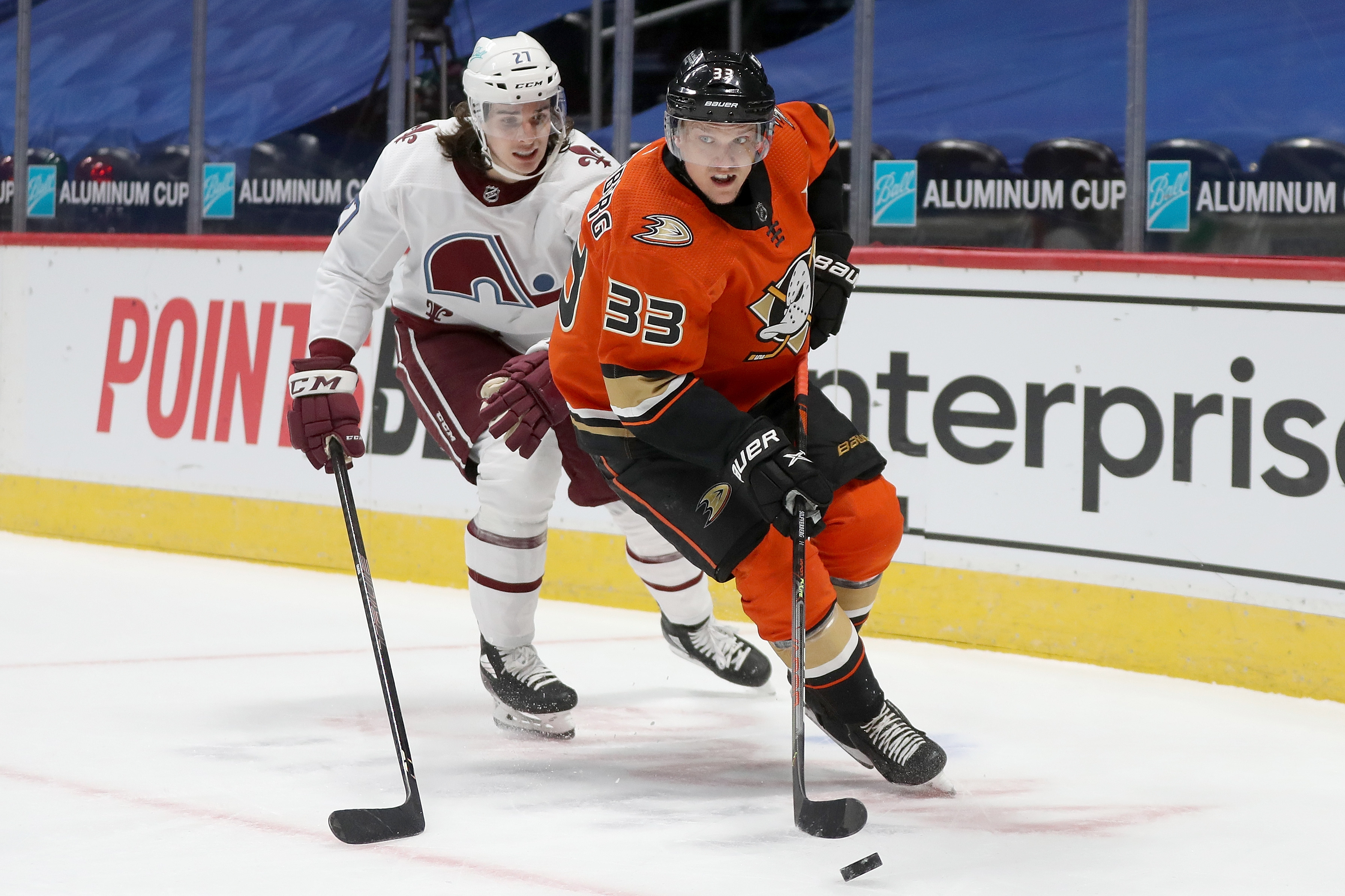 Jakob Silfverberg #33 of the Anaheim Ducks brings the puck off the boards against Ryan Graves #27 of the Colorado Avalanche in the first period at Ball Arena on March 06, 2021 in Denver, Colorado.