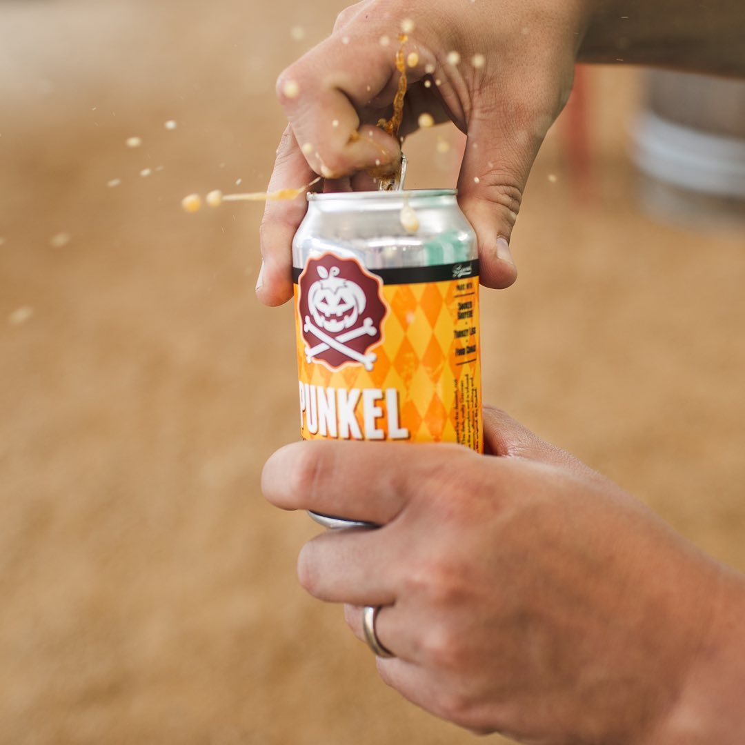 """Two hands holding a can of beer labeled """"Punkel."""" One hand is steadying the bottom while the other opens the pull tab of the beer."""