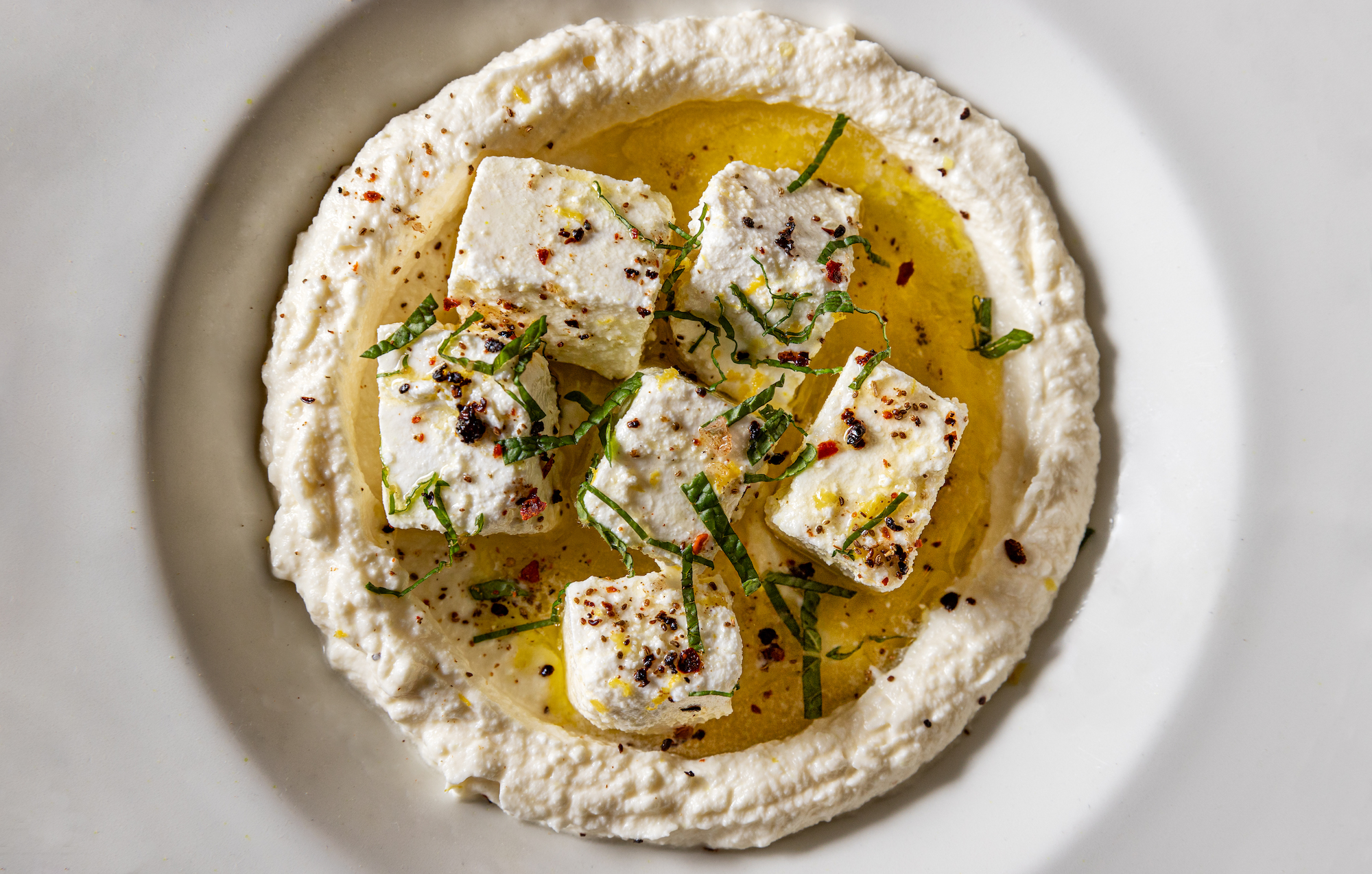 Marinated feta cubes in a blended bowl of more feta from overhead.