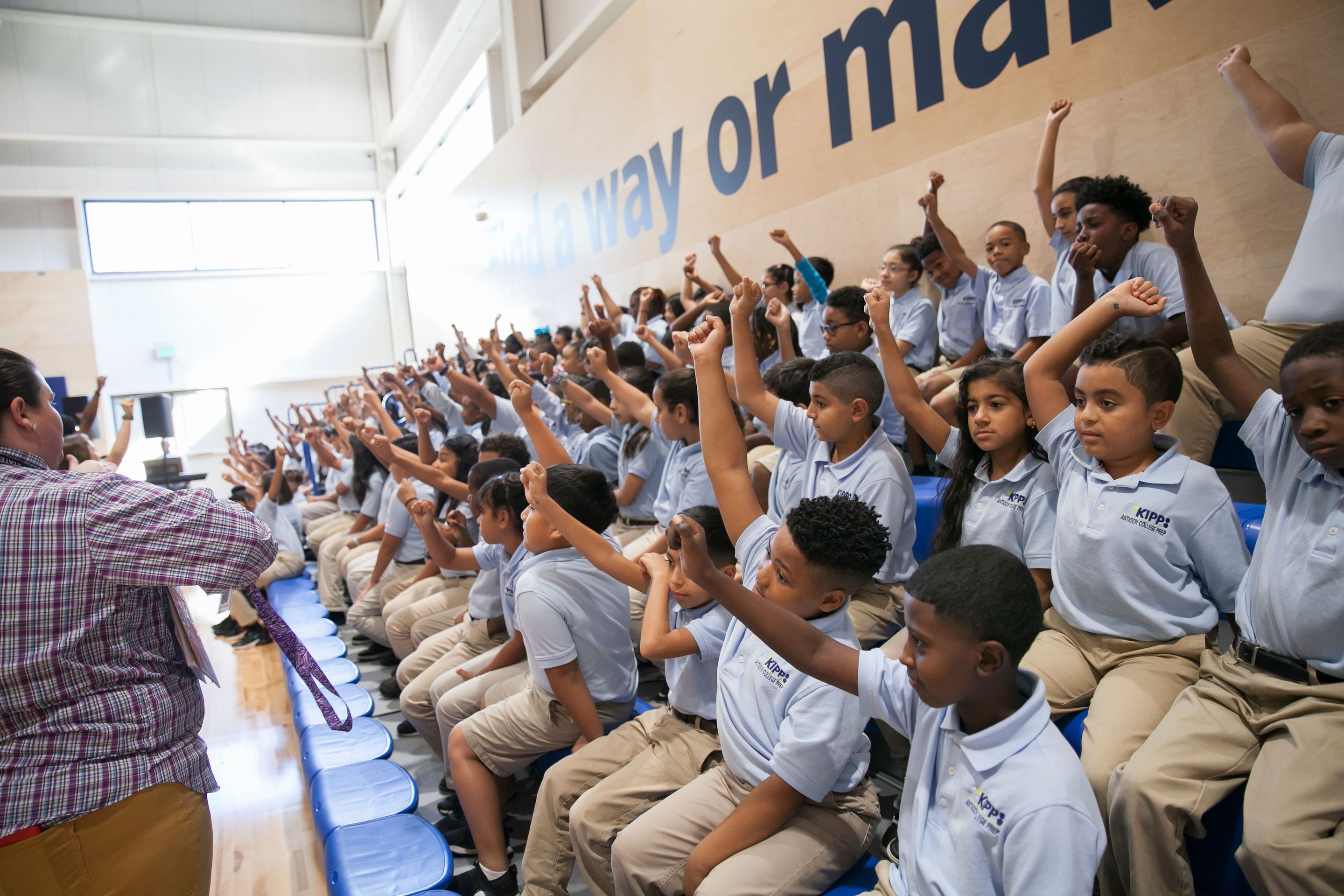 A large group of students, wearing light blue shirts and khaki pants, raise their hands seated on bleachers while educators stand in front of them.