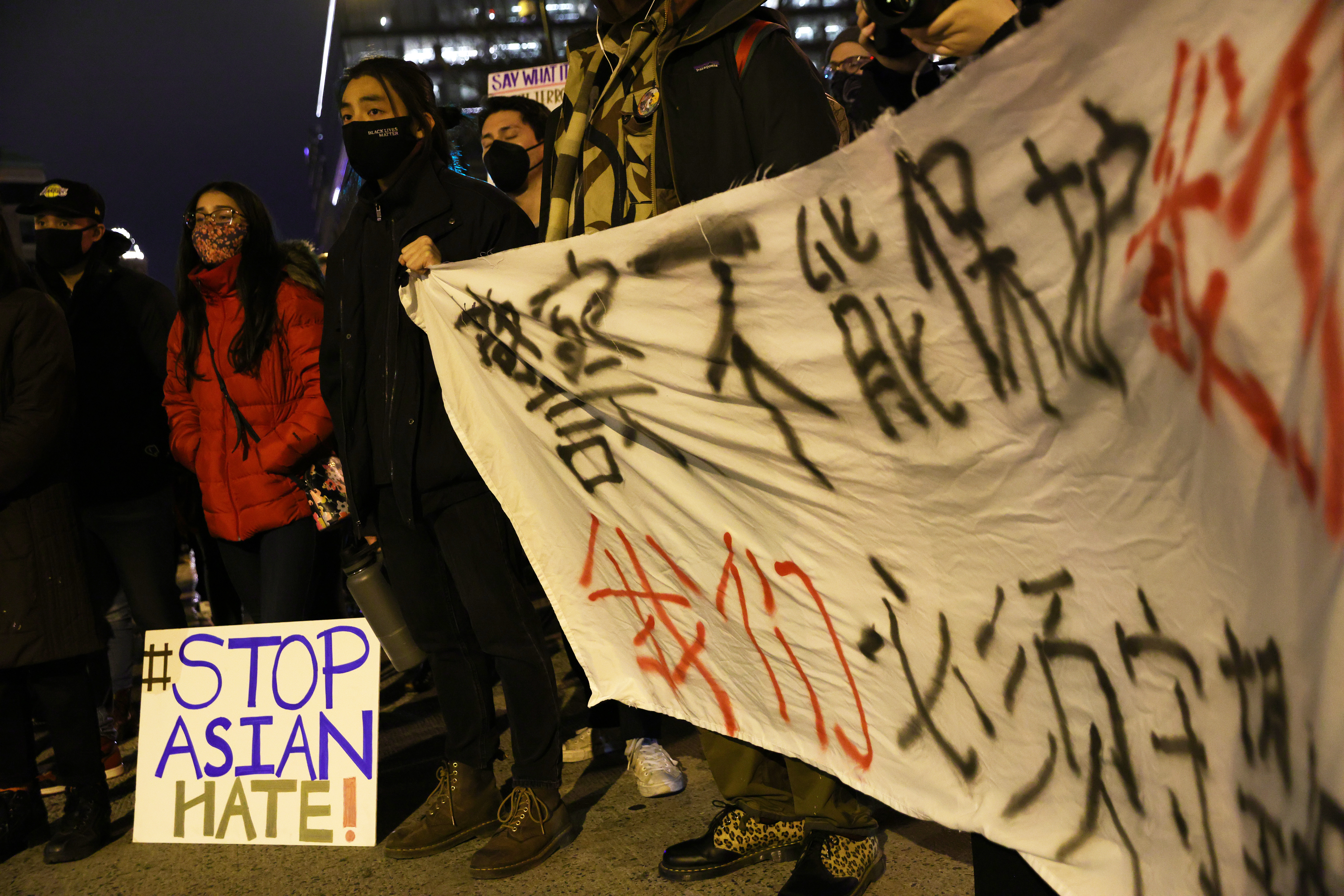 """Activists in Chinatown in Washington, DC, hold up a banner written in Chinese and a sign that reads """"Stop Asian hate."""""""