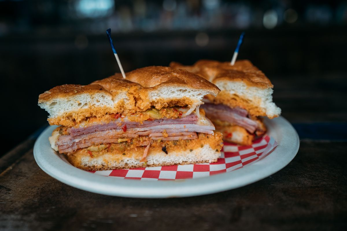 A muffuletta with toothpicks on checkered red and white paper on a white plate.