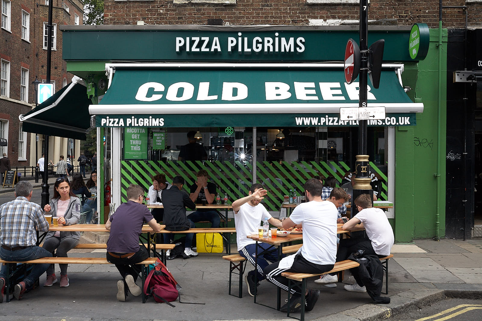 Diners sit outside Pizza Pilgrims