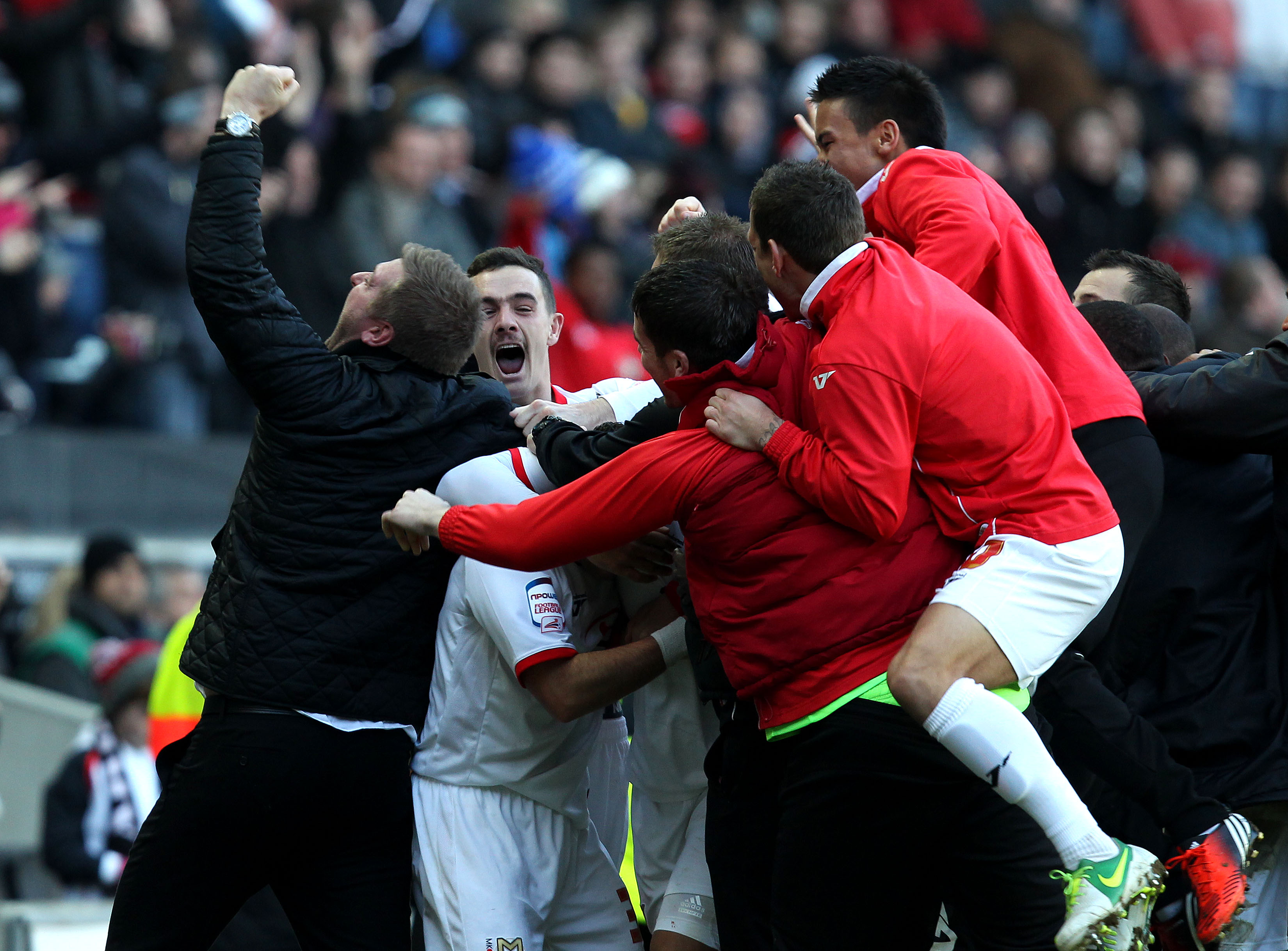 Jon Otsemobor of MK Dons is mobbed by team mates - FA Cup