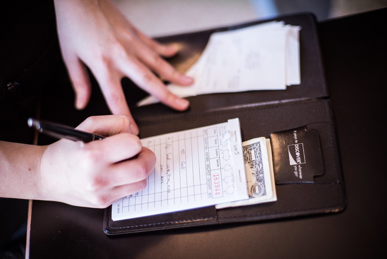 Two hands on a restaurant check holder.