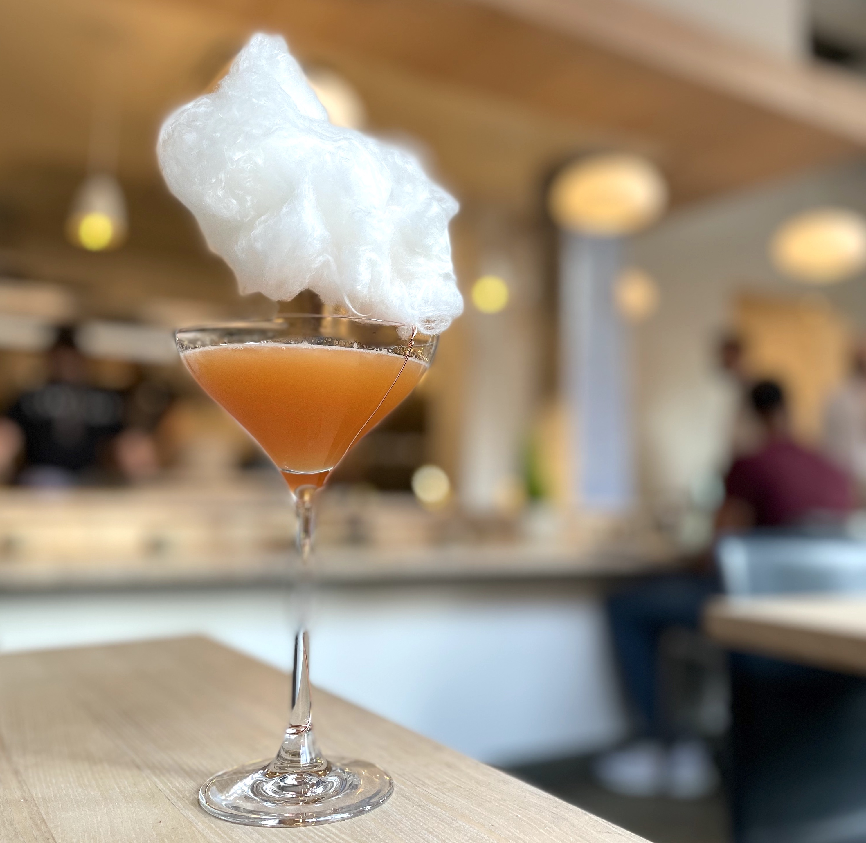 A martini glass is filled with orange liquid on a blonde wood table. It appears that there is a floating cloud above the glass