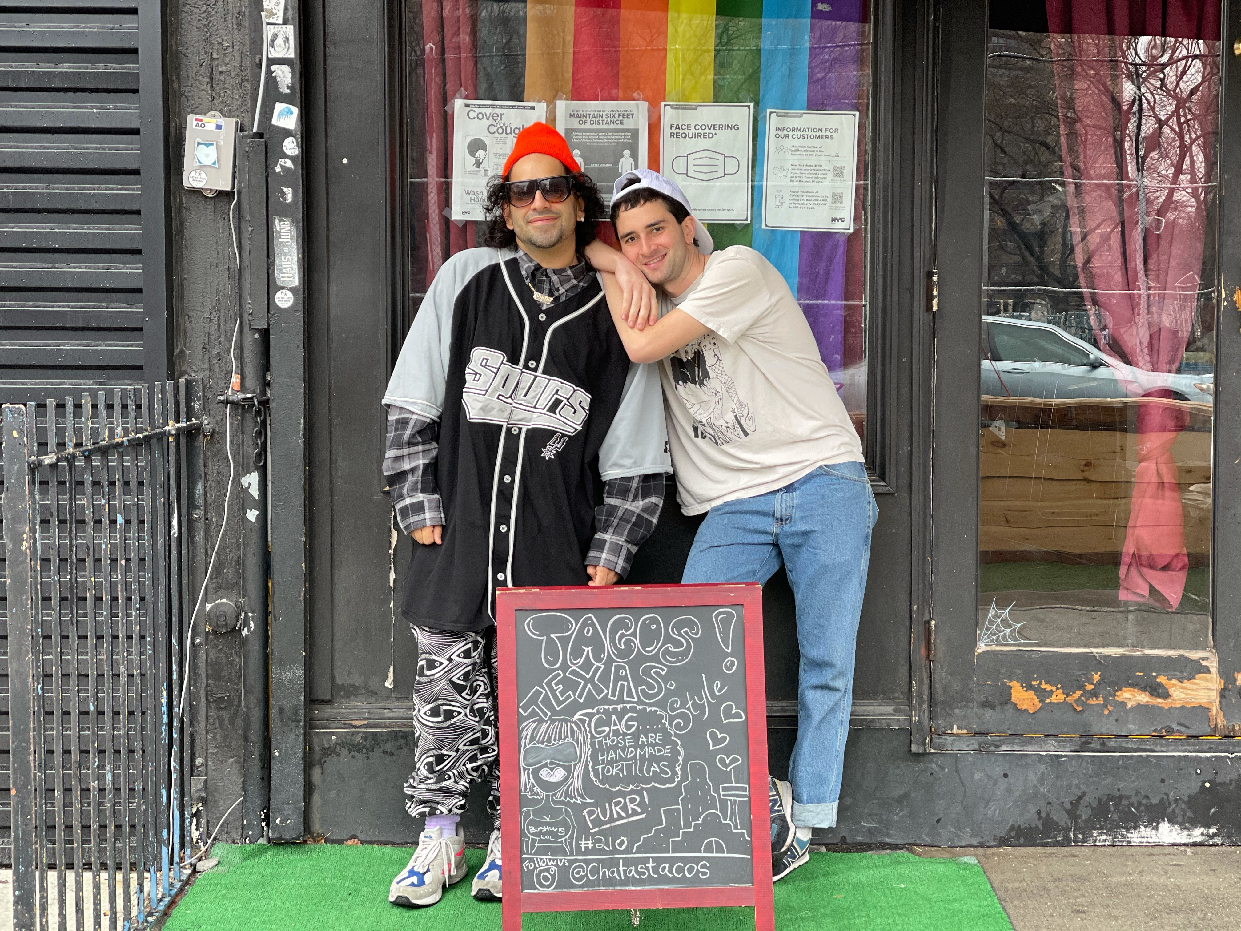Two people are standing next to each other in front of a store with a signboard at their feet