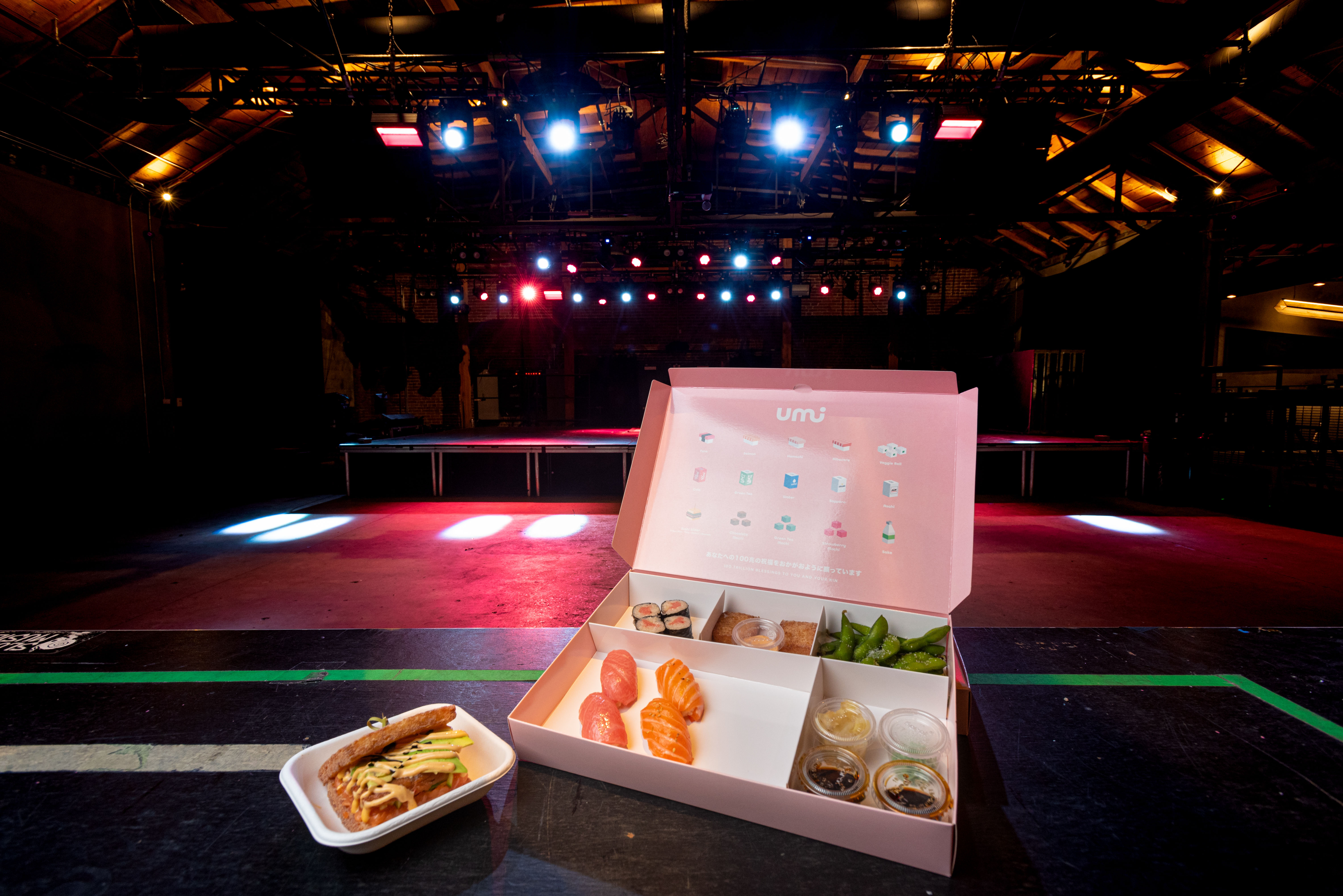 box of sushi sits in front of a colorful stage in a dark venue.