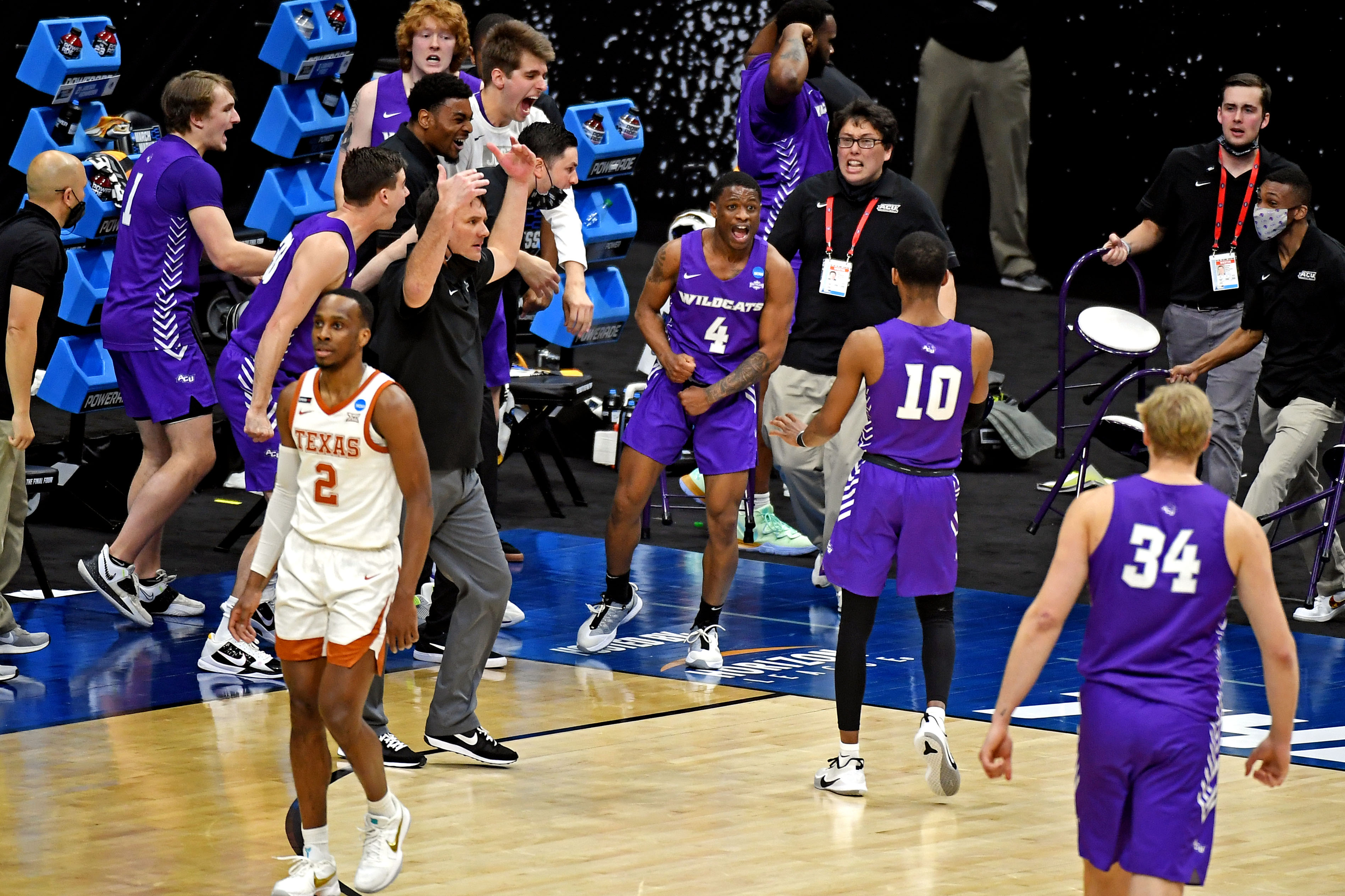 The Abilene Christian Wildcats bench reacts after a play during the second half against the Texas Longhorns in the first round of the 2021 NCAA Tournament at Lucas Oil Stadium.