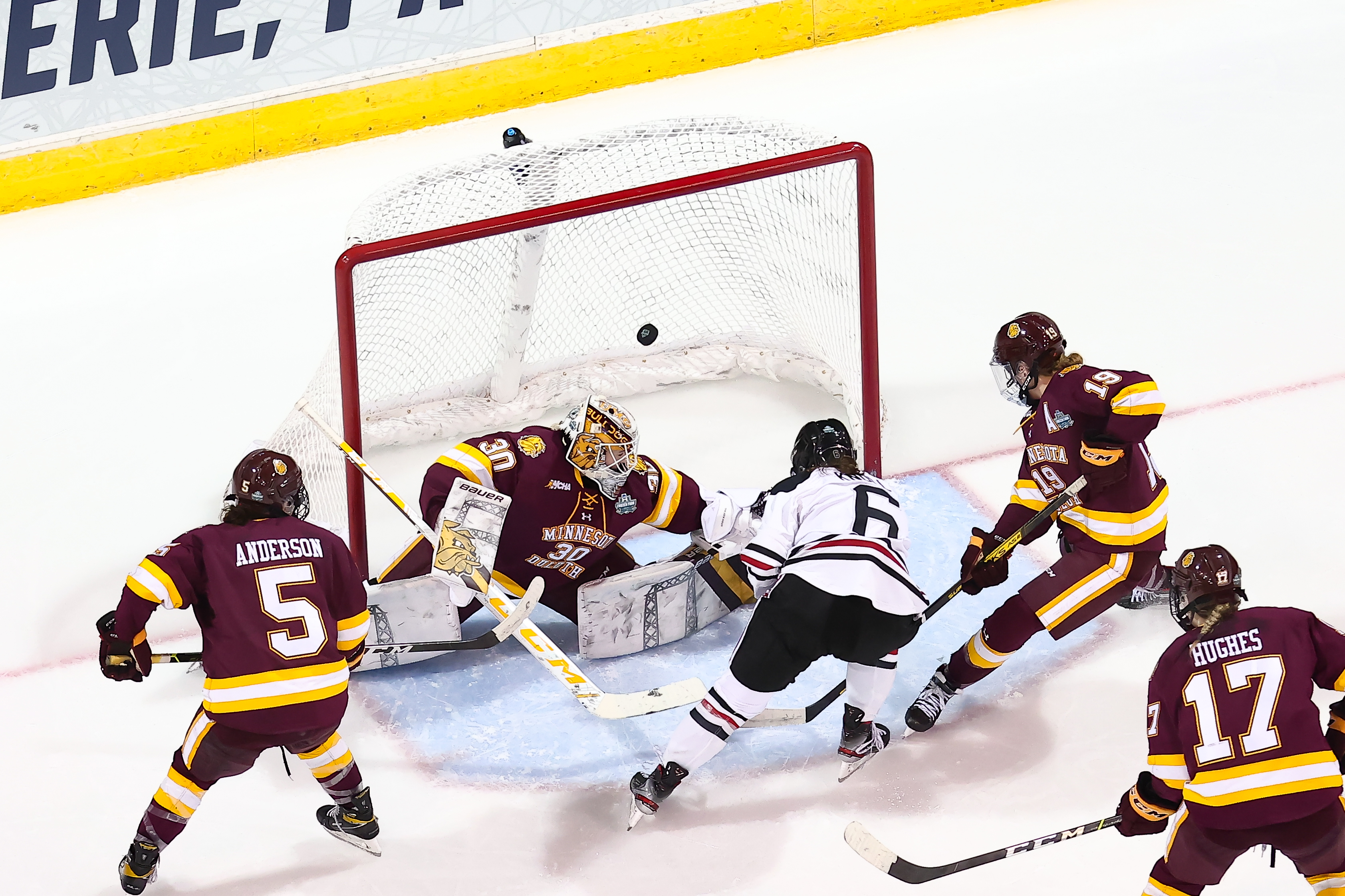 Northeastern's Katy Knoll watches her shot fly past Minnesota Duluth's goaltender as she crashes the net, surrounded by three Bulldogs players.