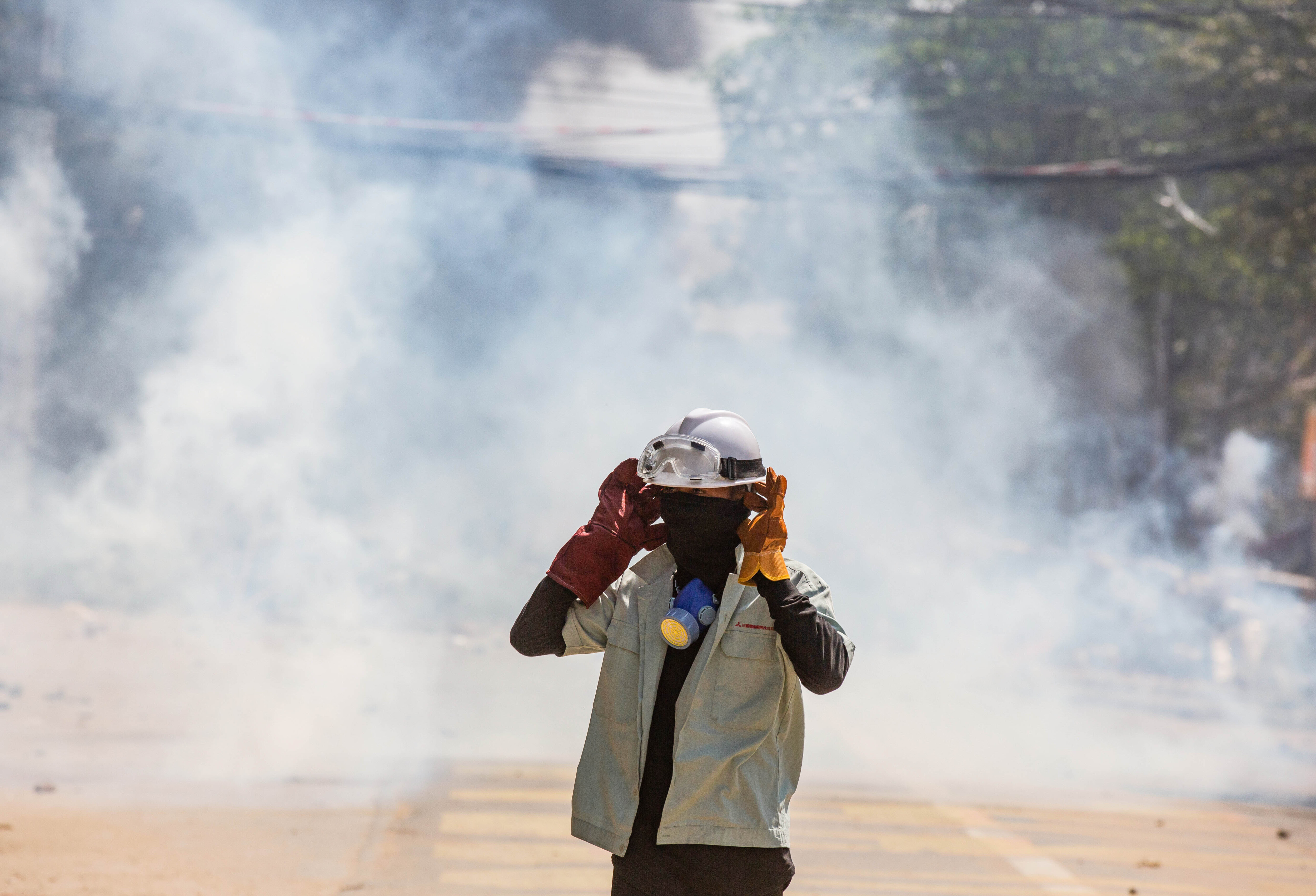 An anti military coup protester stands in the middle of teargas smoke during a demonstration in Myanmar
