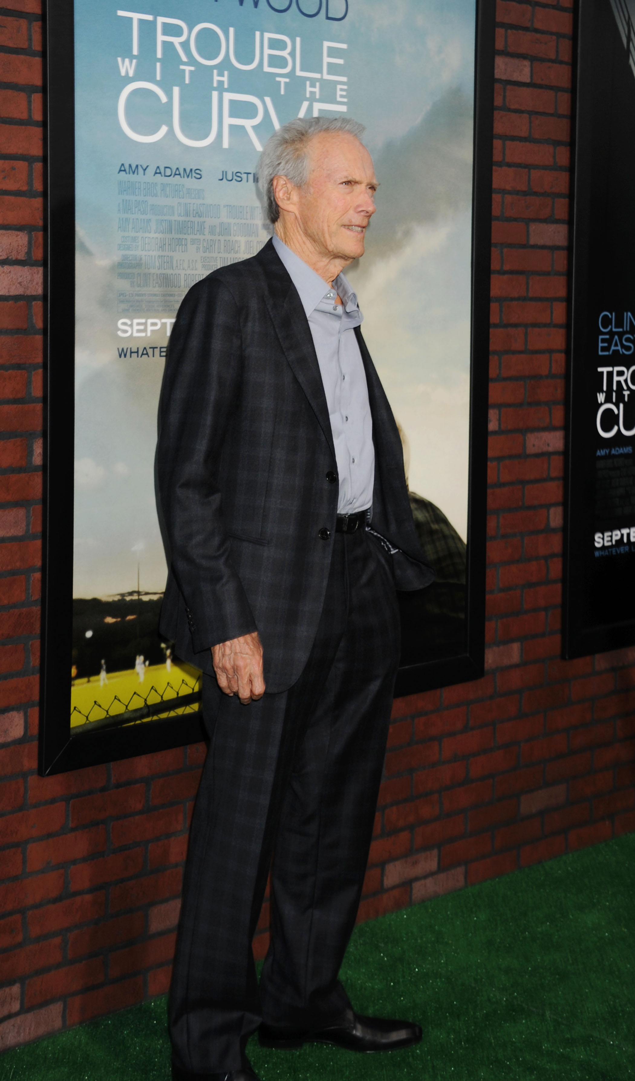 Clint Eastwood standing in front a poster for Trouble with the Curve