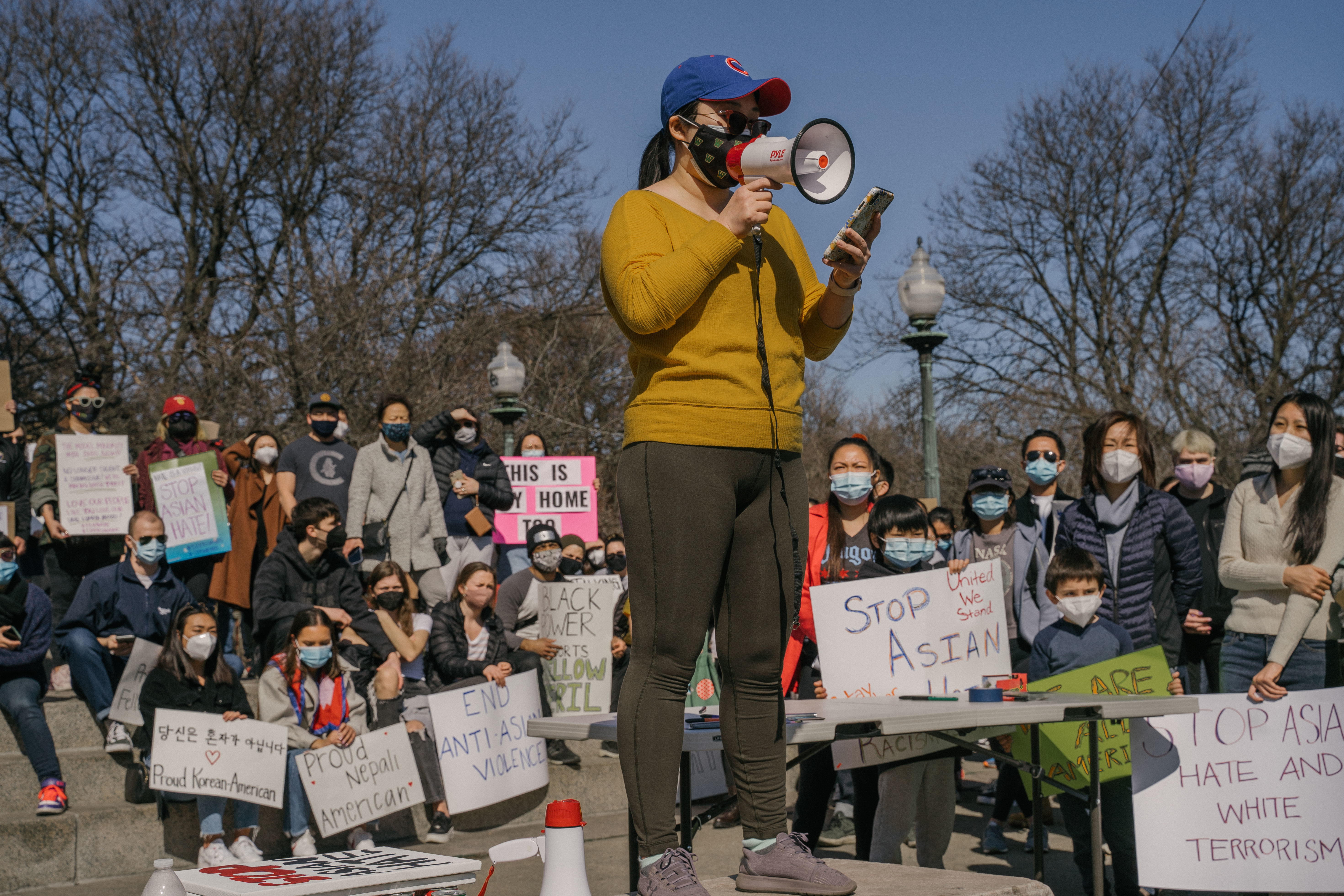 Qiong Chen, a teacher at Westinghouse College Prep, speaks to the crowd with a megaphone during the Stop Asian Hate March at the Illinois Centennial Monument in Logan Square, Saturday afternoon, March 20, 2021.