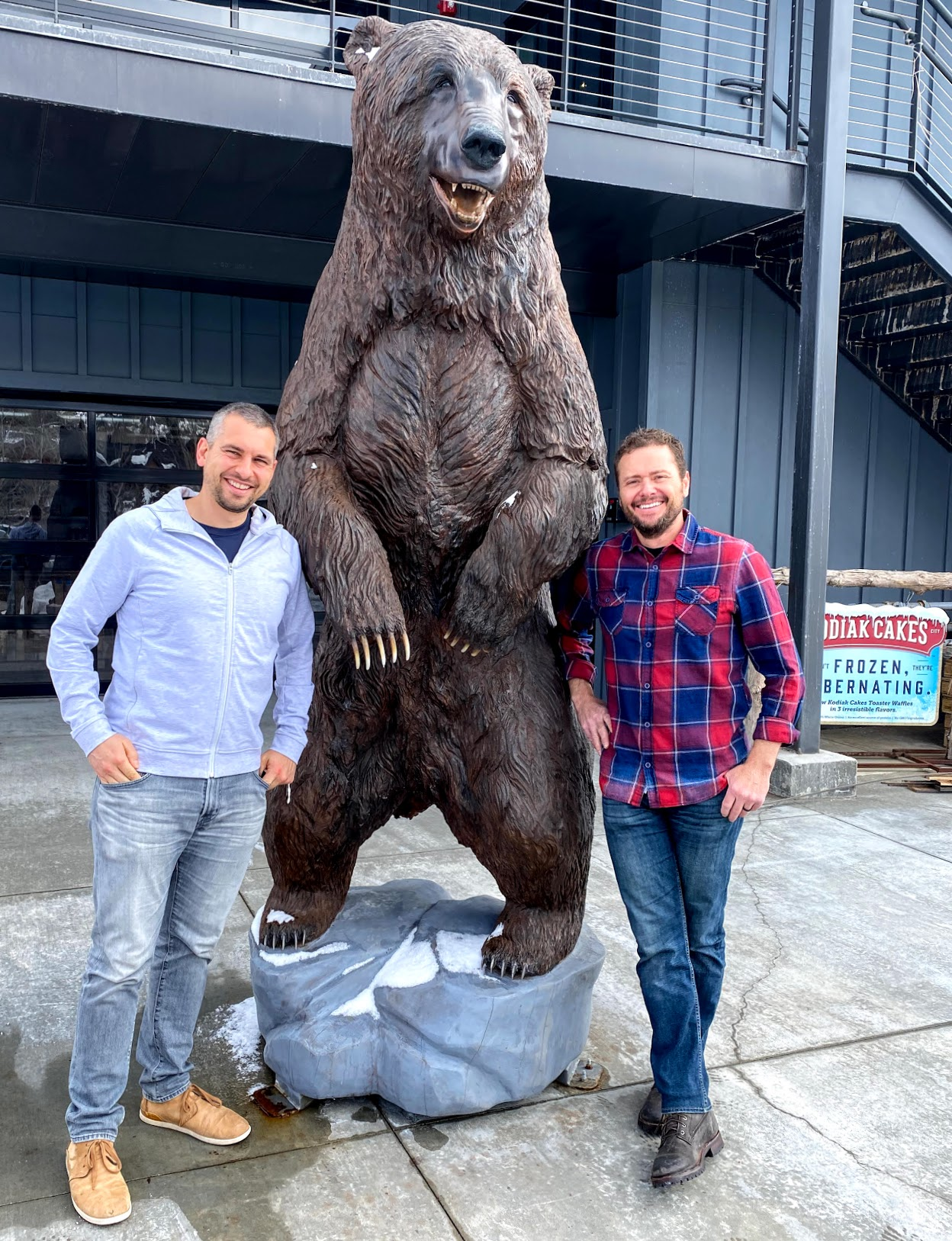 Kodiak Cake President Cameron Smith, left, and CEO Joel Clark pose with Kodiak the bear in front of the company's headquarters in Park City.