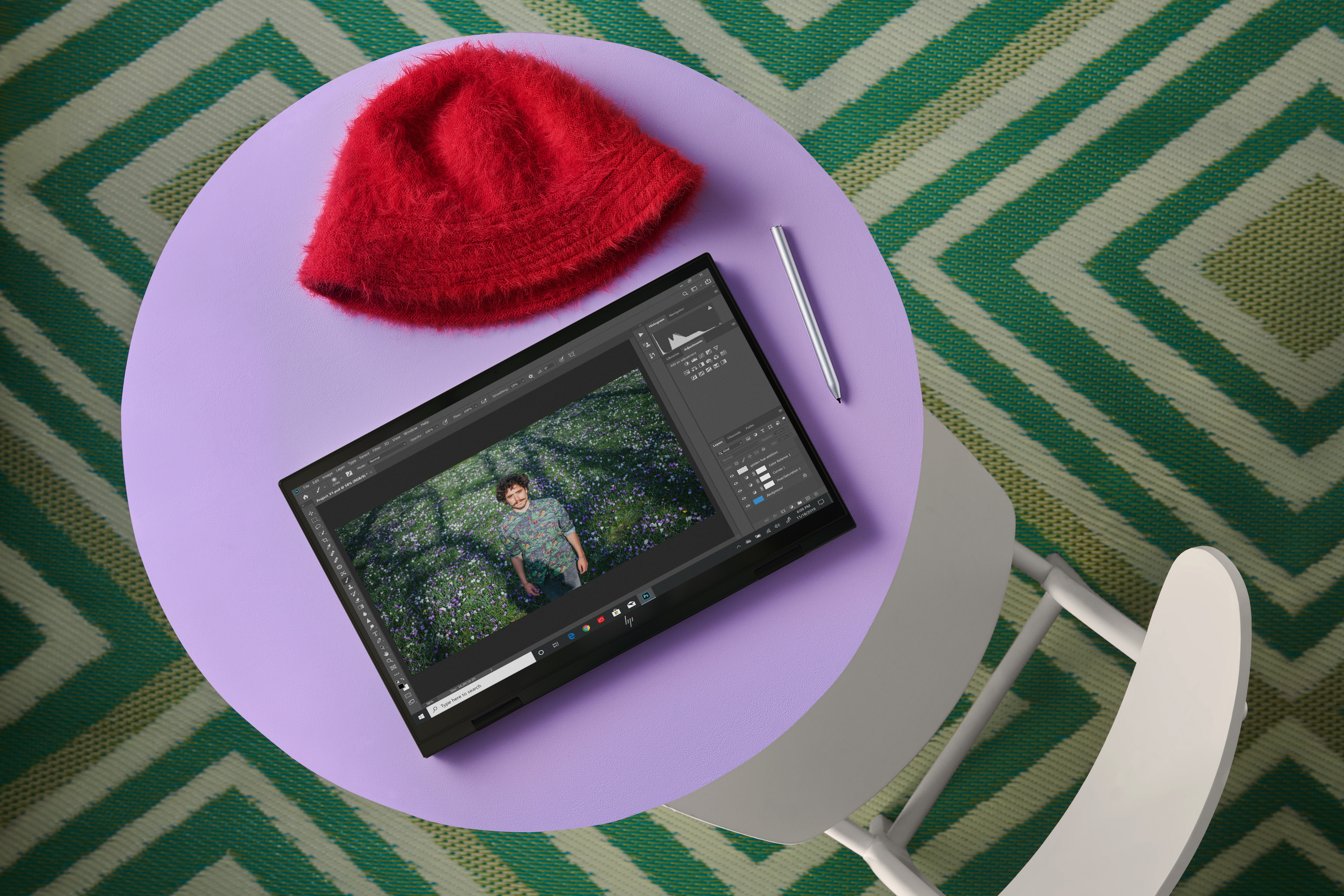 The HP Envy x360 15 in tablet mode on a purple desk. Above it is a red beanie and to its right is a stylus. The screen displays a photo editing software. The carpet has a green square pattern.