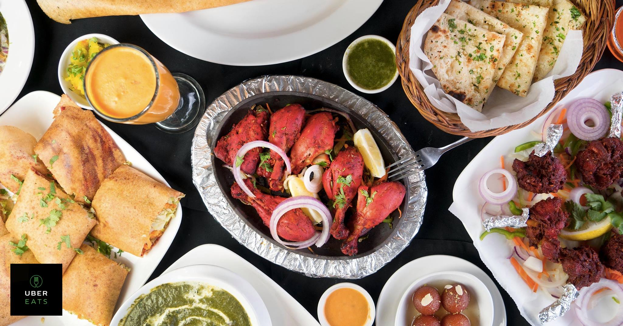 Tandoori chicken, mango lassi, blistered naan, aloo, and more food spread out on a table