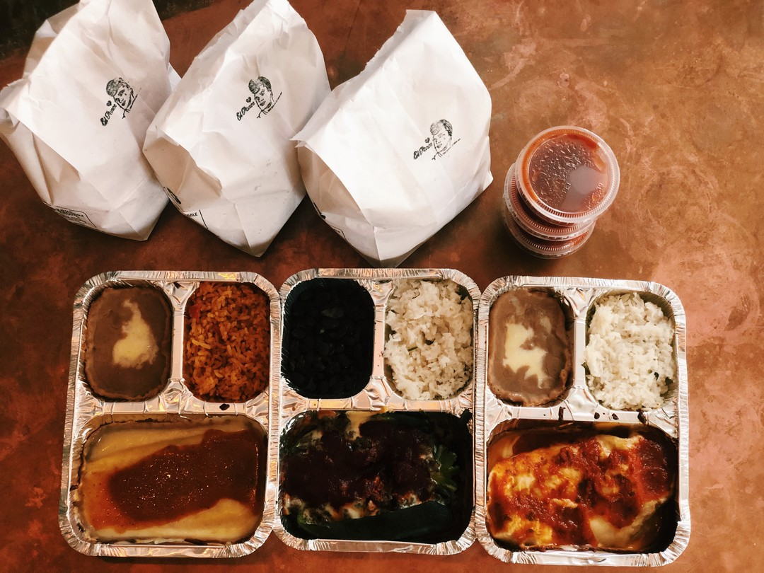 Three sectioned tin takeout containers with rice and refried beans and three Mexican entree dishes. Three white bags of chips with a stamped El Ponc logo sit beside a stack of three plastic containers of red salsa