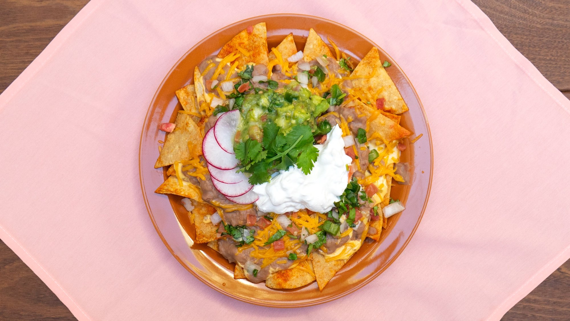 An overhead bowl of cheesy nachos with beans and sour cream, on a pink table.