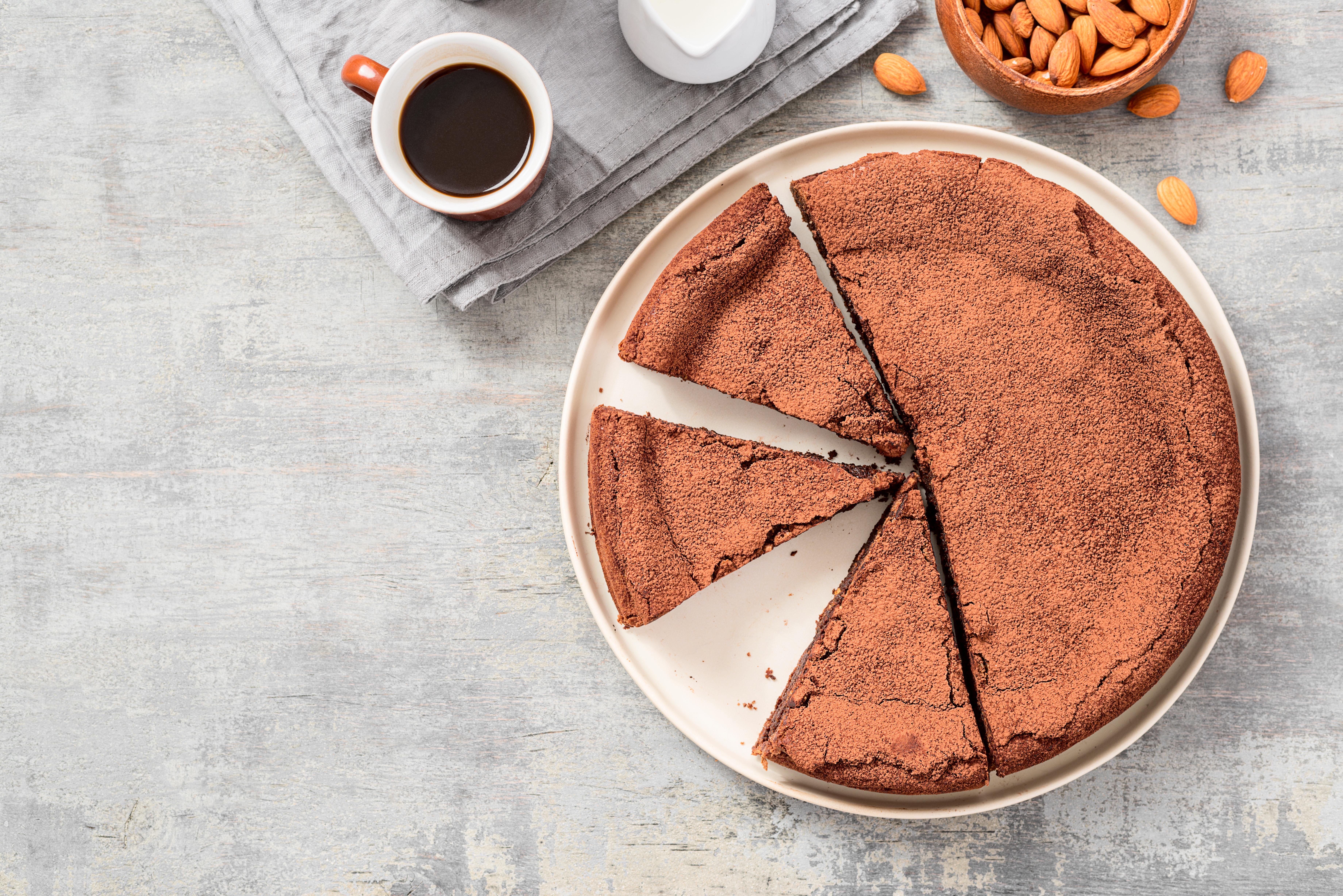 A flourless chocolate cake, seen from above, sits on a table next to a cup of coffee and a bowl of almonds.