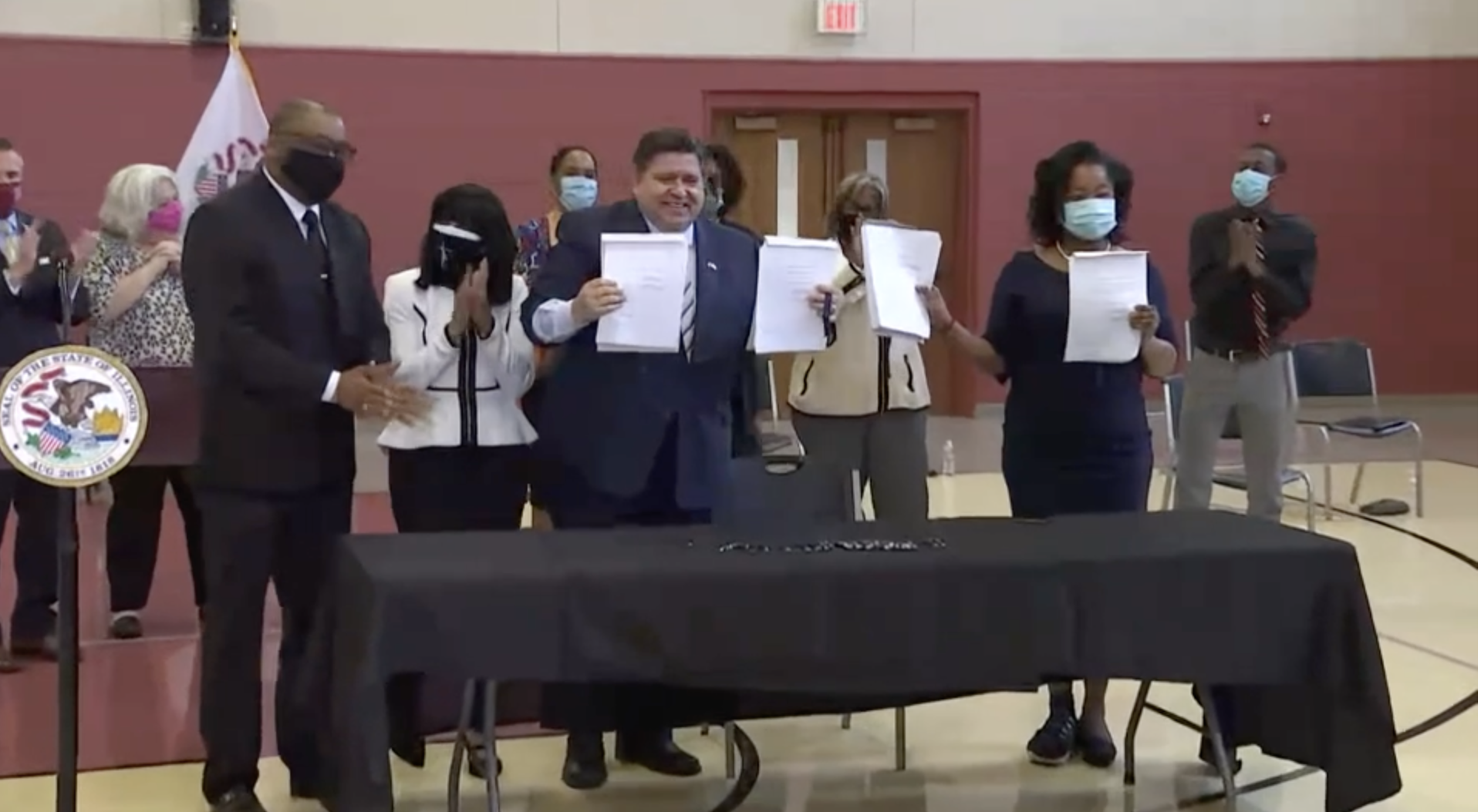 Gov. J.B. Pritzker and state Rep. Sonya Harper hold up signed legislation related to the Illinois Legislative Black Caucus' agenda addressing economic access, equity and opportunity that Pritzker signed Tuesday.
