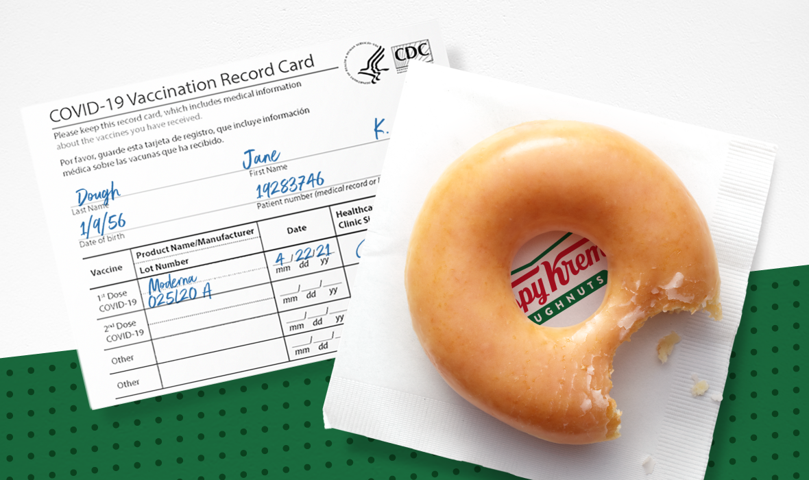 """A glazed donut with a bite taken out of it sits on top of a Krispy Kreme napkin and a COVID-19 vaccination card filled out with the name """"Jane Dough."""""""
