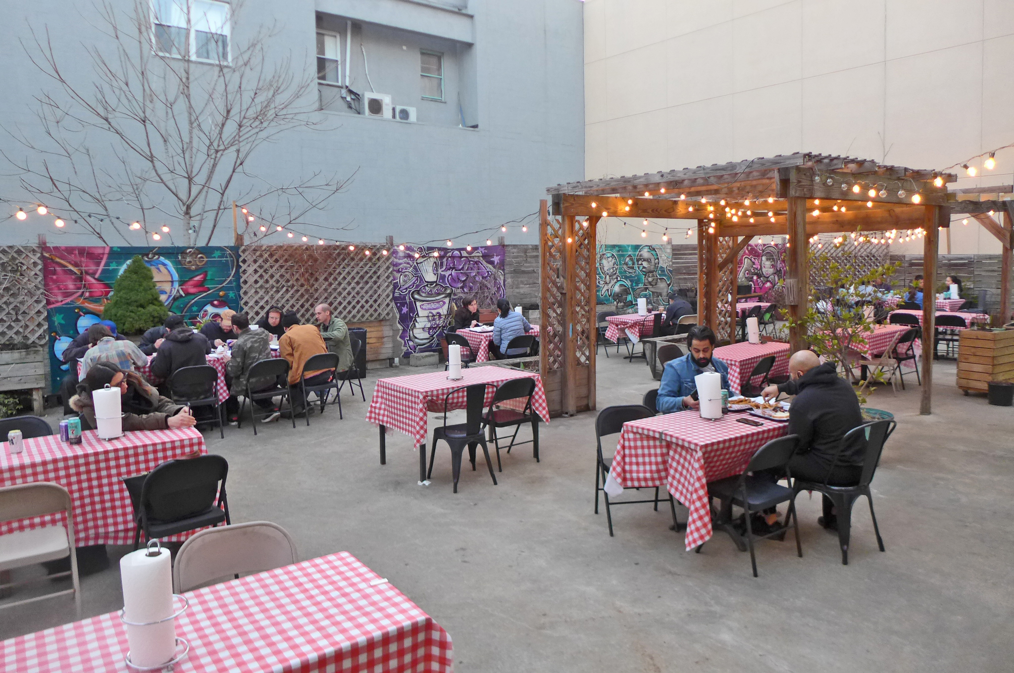 A courtyard with nicely spaced tables, half occupied, with red-checked tablecloths and strings of lights overhead.
