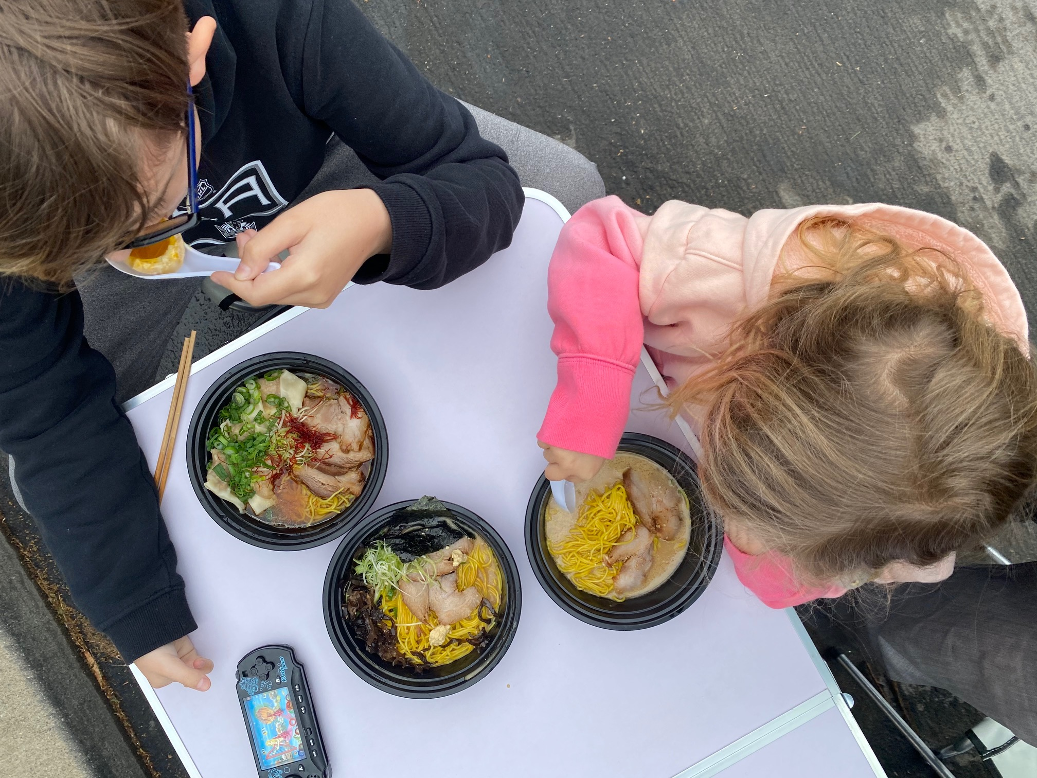 An overhead shot of two children with bowls of noodles at a folding table