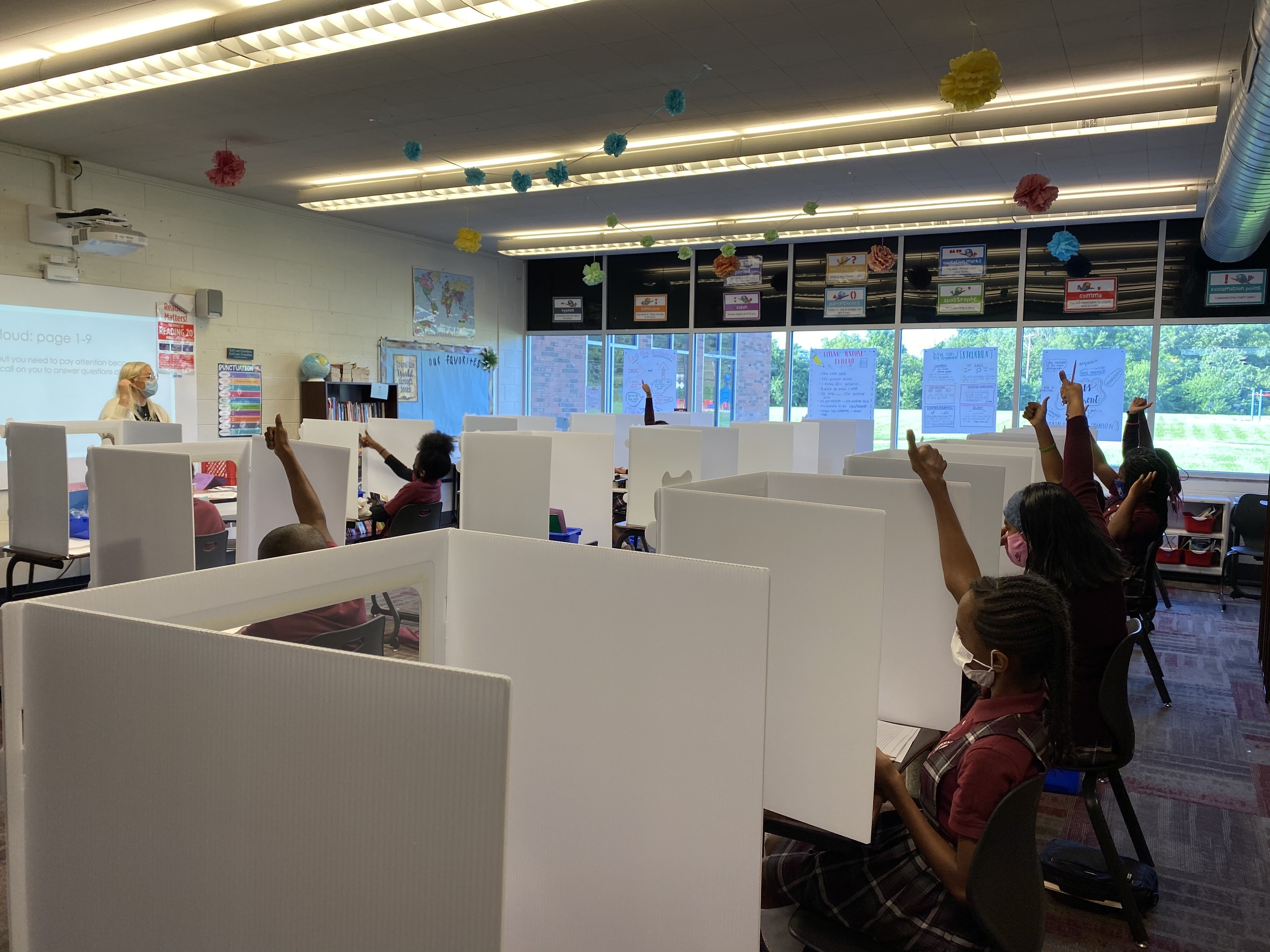 Students separated by partitions raise their hands during class. The teacher stands at the front.