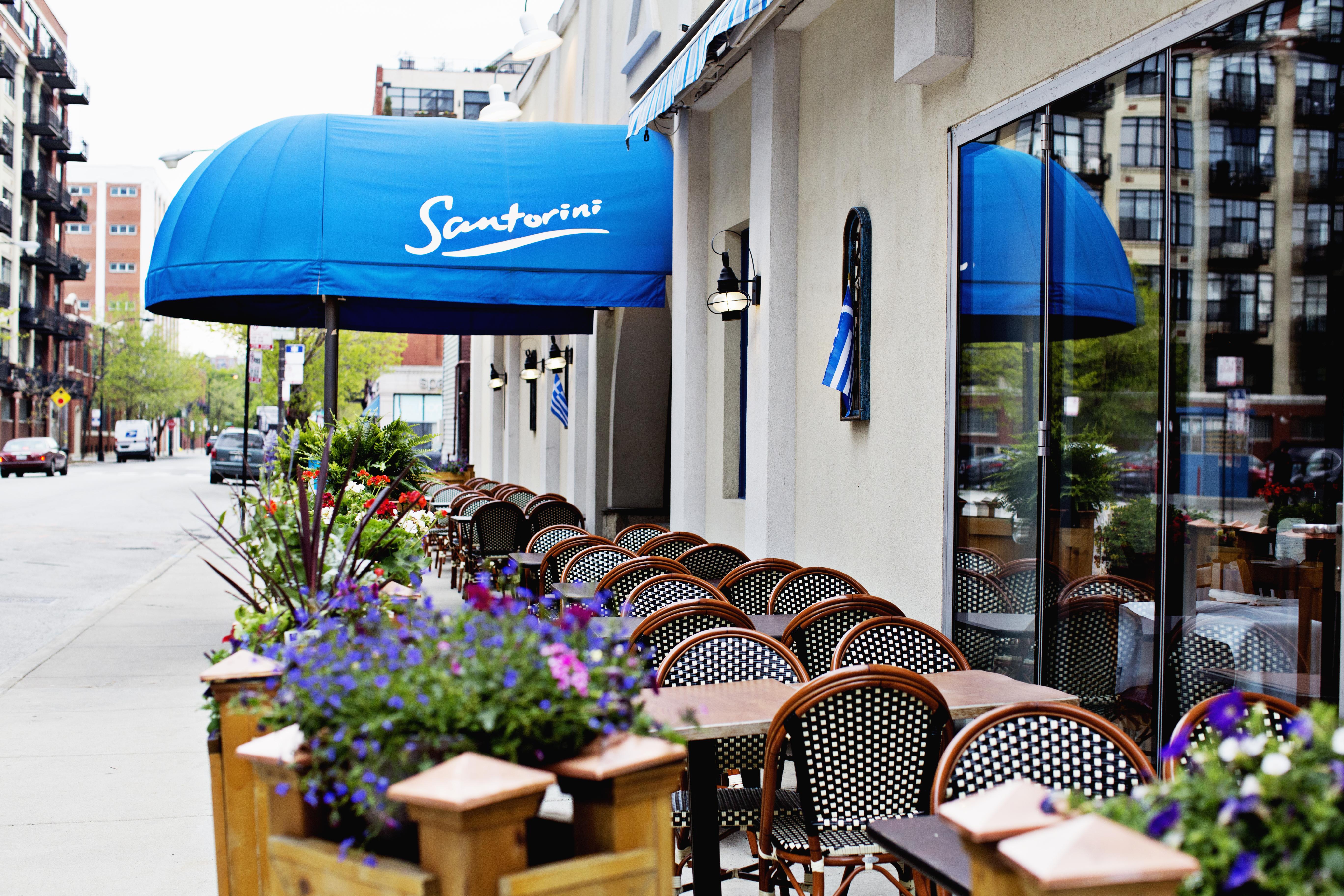 A restaurant's blue awning behind its sidewalk patio.