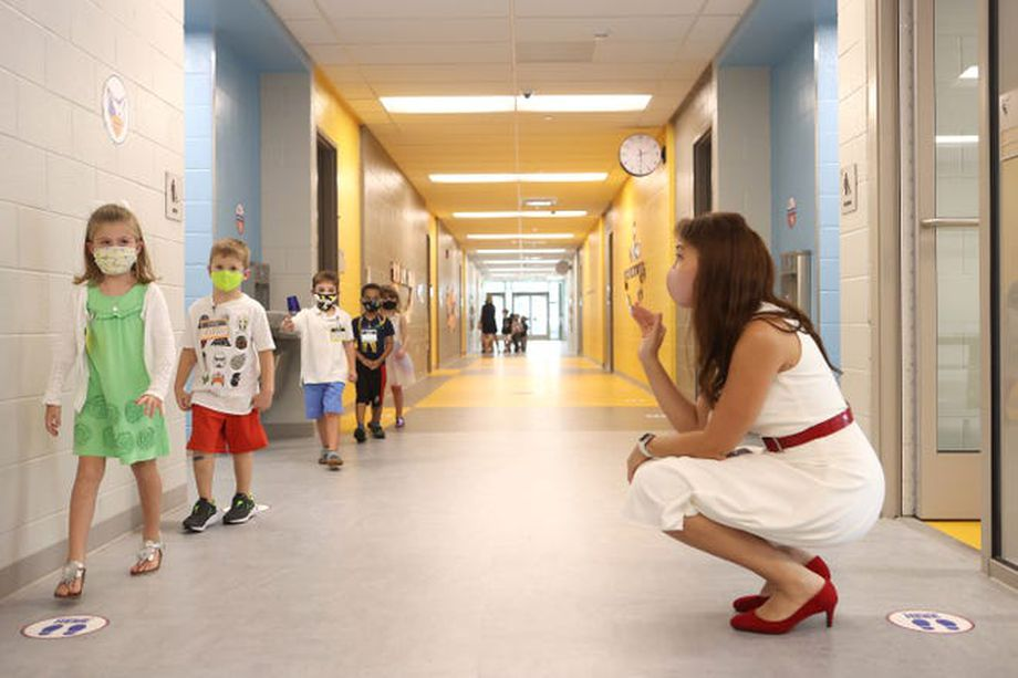 Woman in white sleeveless shift with red patent belt and shoes squats in school hallway, waving at a line of elementary children walking past.