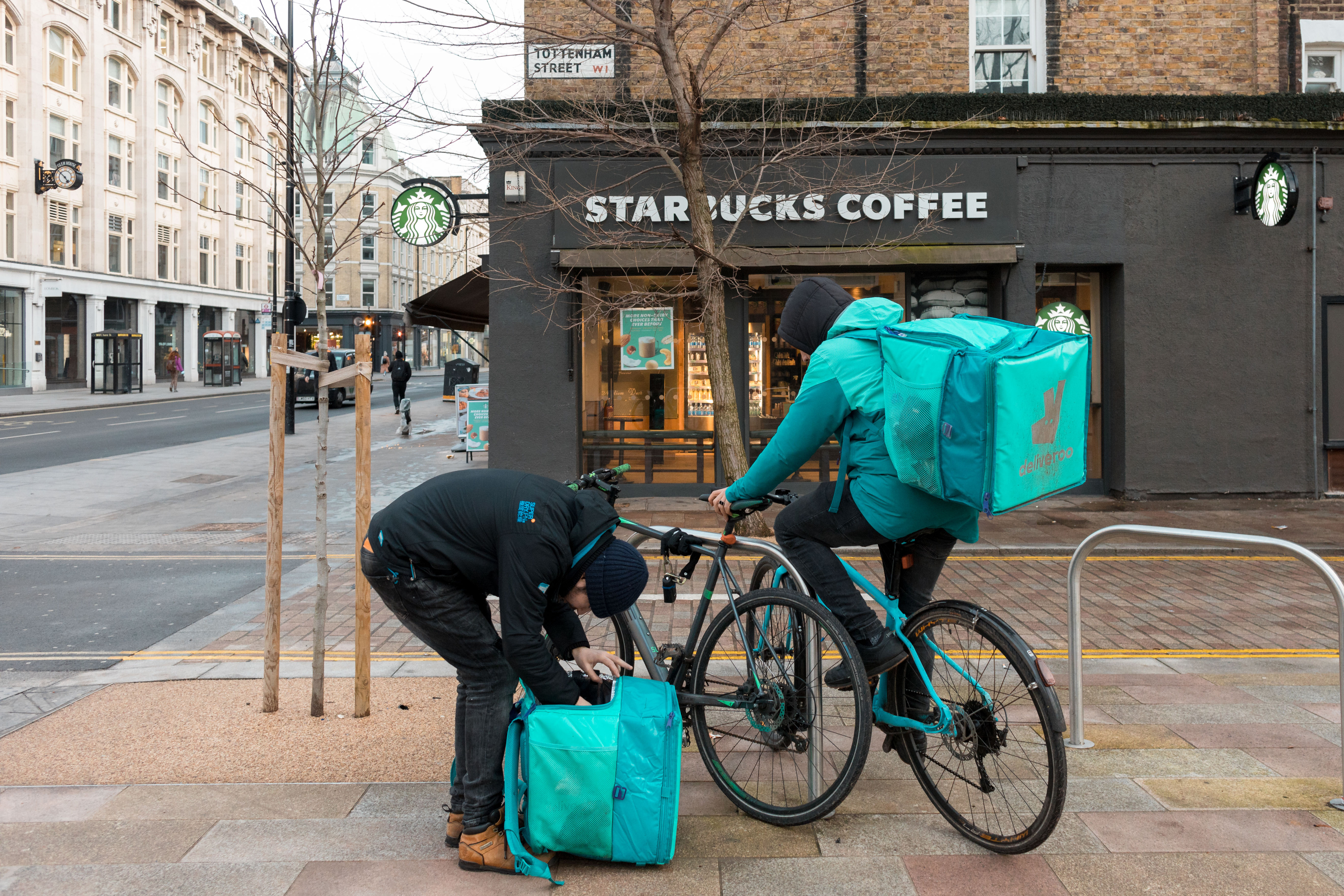 Two Deliveroo riders seen in front of a Starbucks coffee store in London