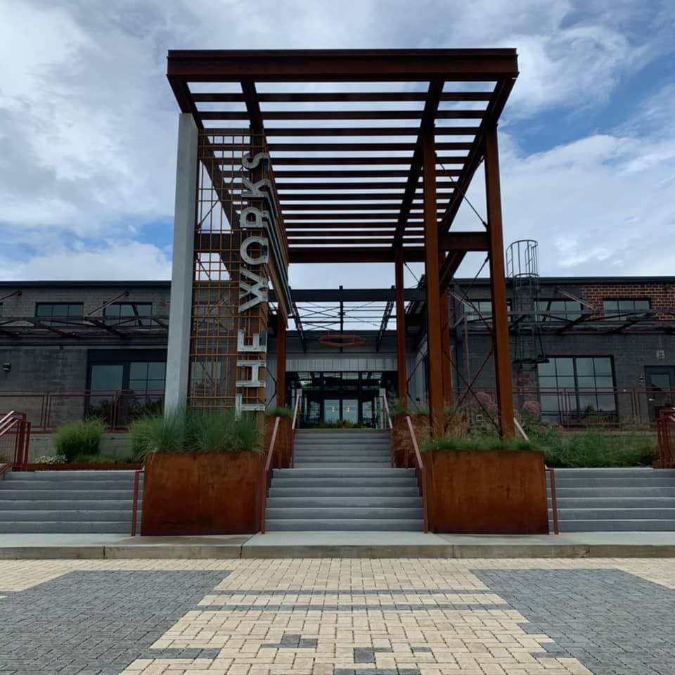 """The outside entrance to the food hall Chattahoochee Food Works with faux rusted metal entryway and """"The Works"""" along the left side leading up a set of concrete stairs into the old warehouse building"""