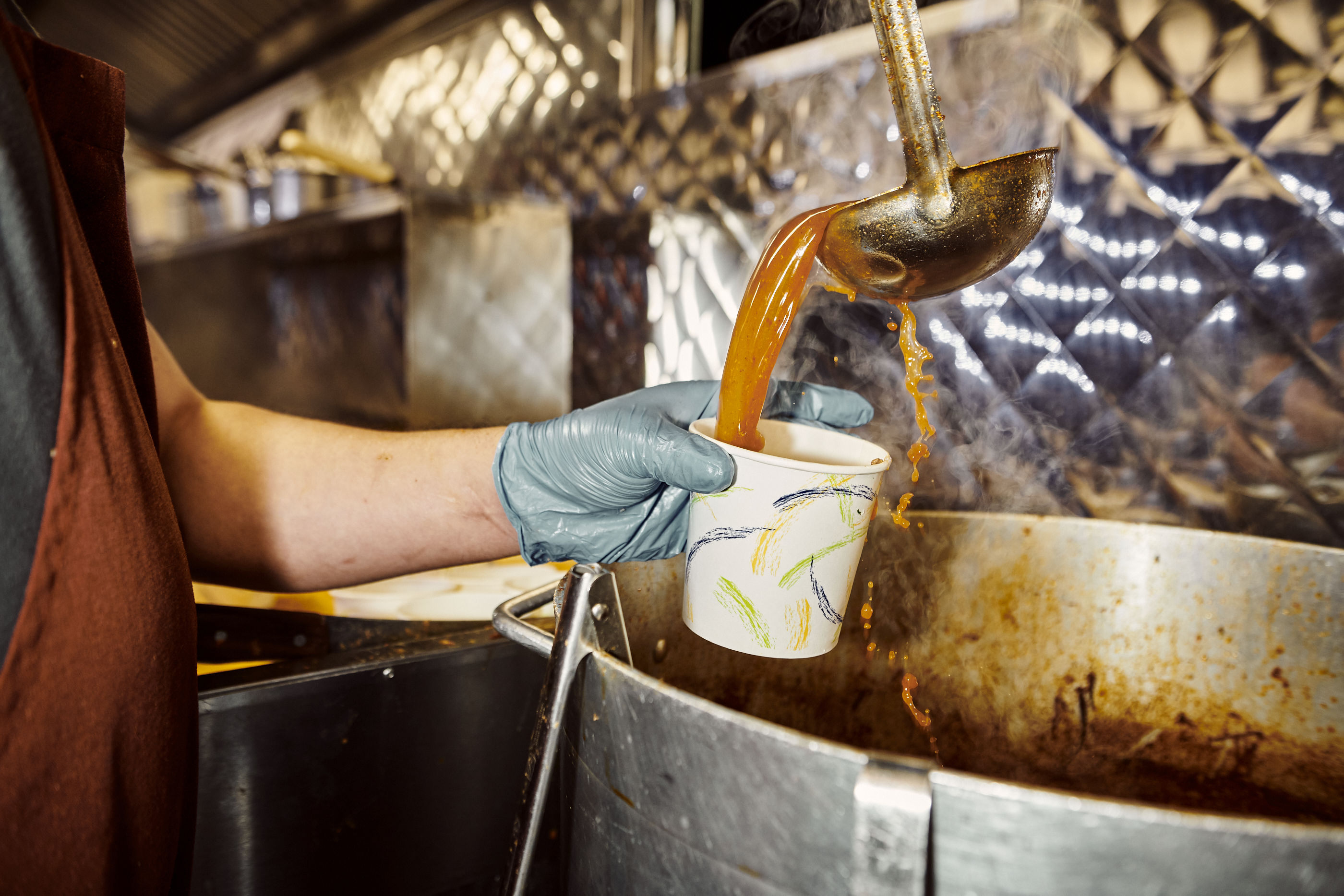 A chef ladles a scoop of orange consomme into a takeout cup held by a hand wearing a mint-colored glove