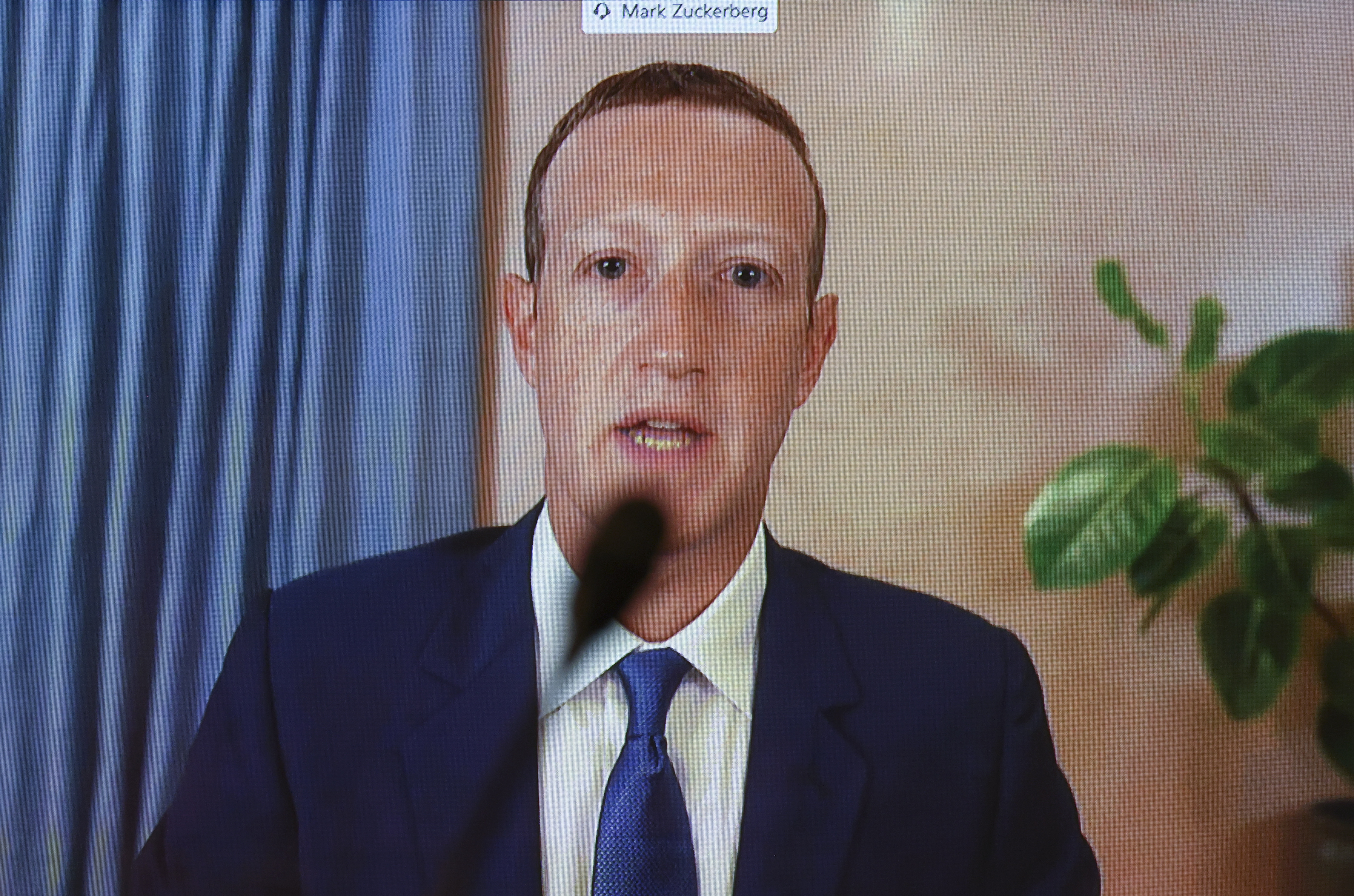 A screenshot of Mark Zuckerberg talking into a microphone via videochat.