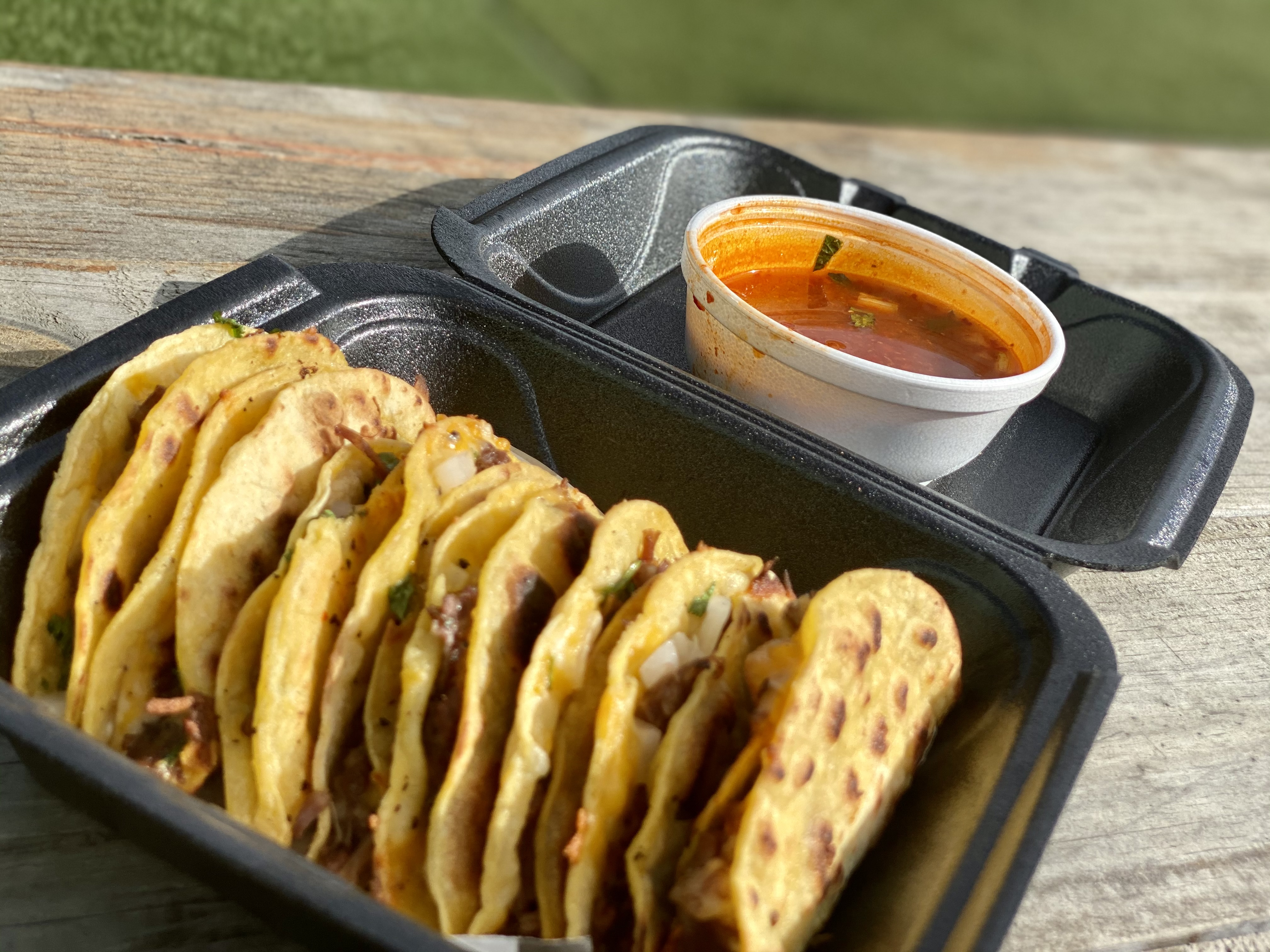 Six birria tacos sit neatly in a row inside a black styrofoam takeout container. A cup of red consomme sits beside the tacos in the top lid of the container