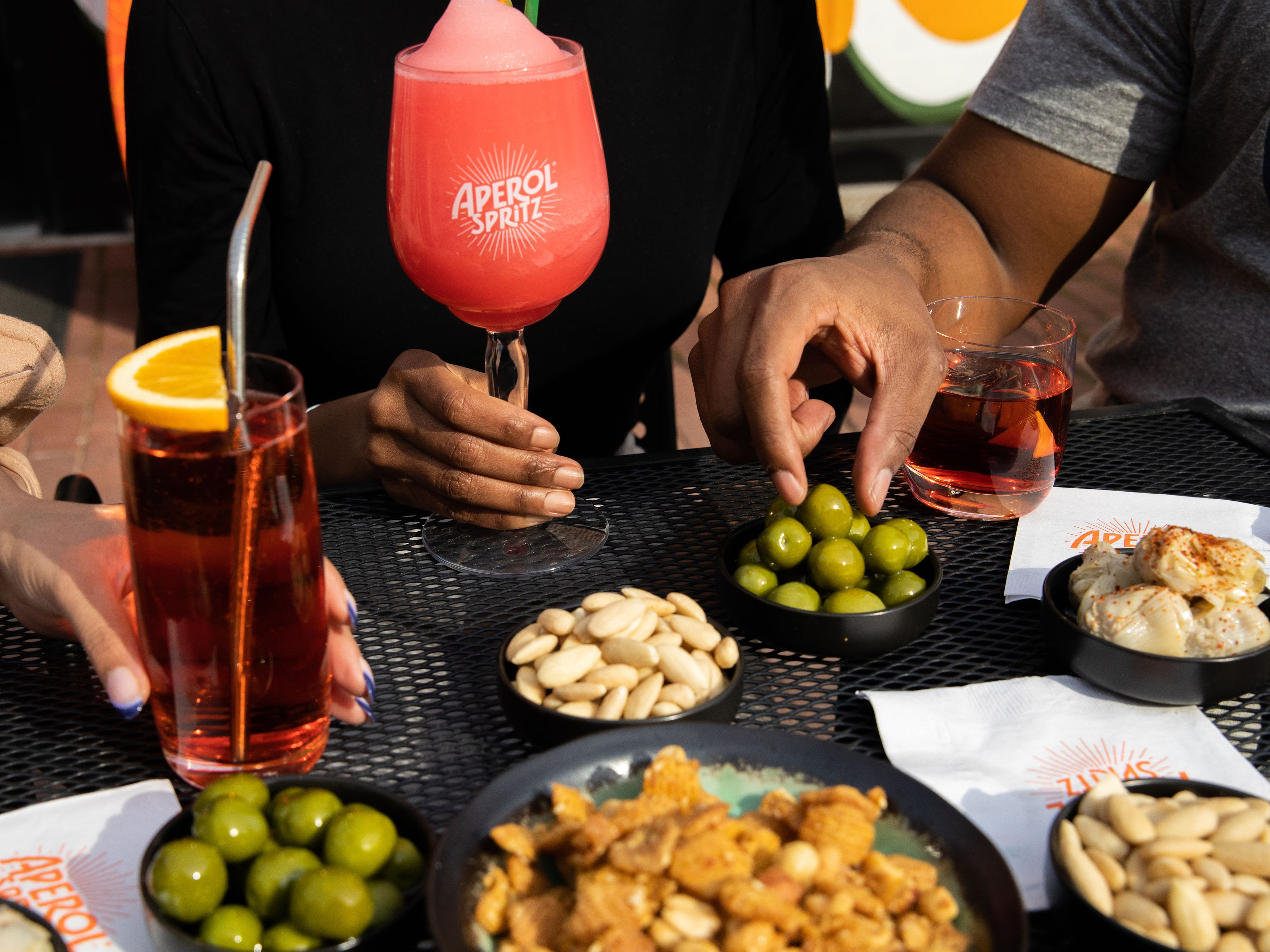 Aperol cocktails get paired with olives, marinated artichoke hearts, meatballs, and whipped gorgonzola.
