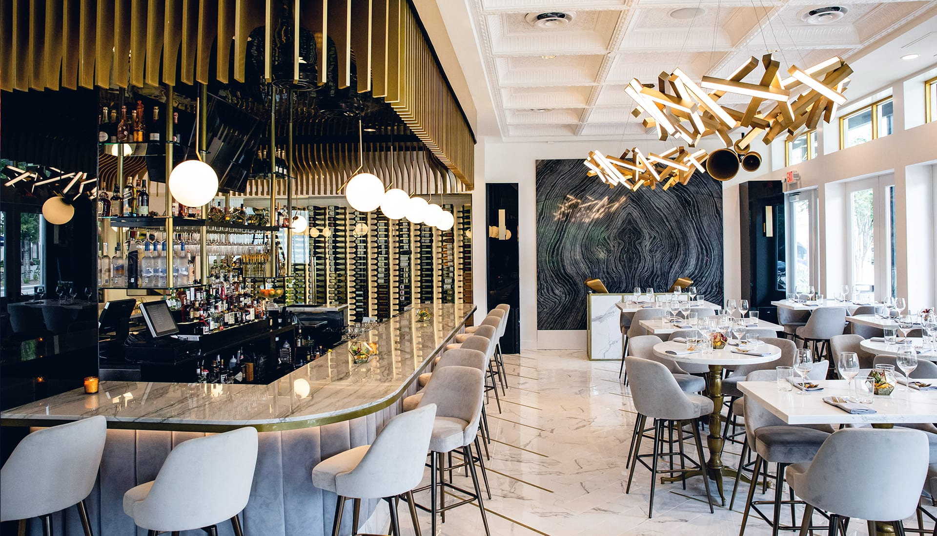 A glamorous dining room with white marble tops, tall upholstered chairs, and gold accents