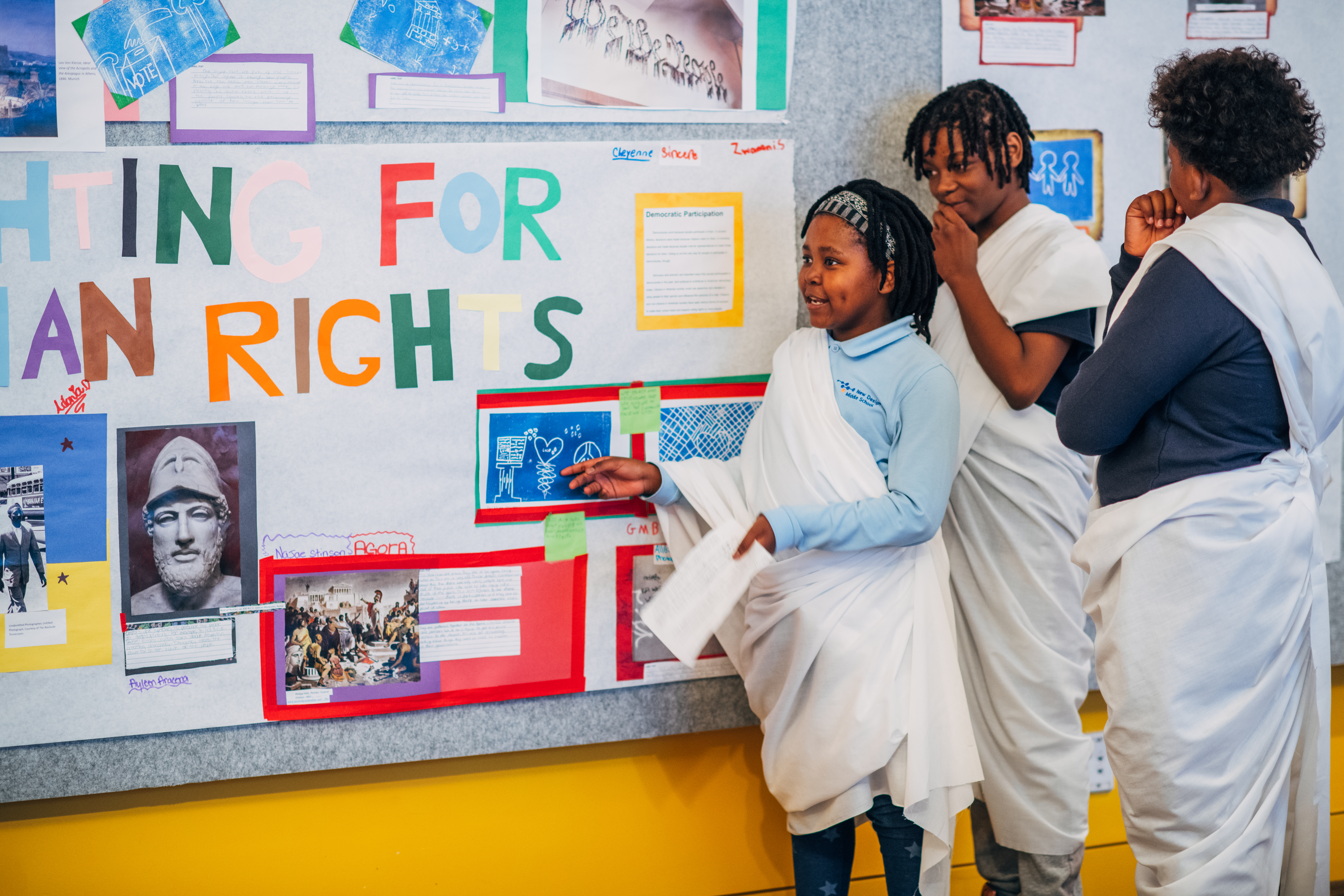 Three students look at a classroom wall display with information about American democracy.