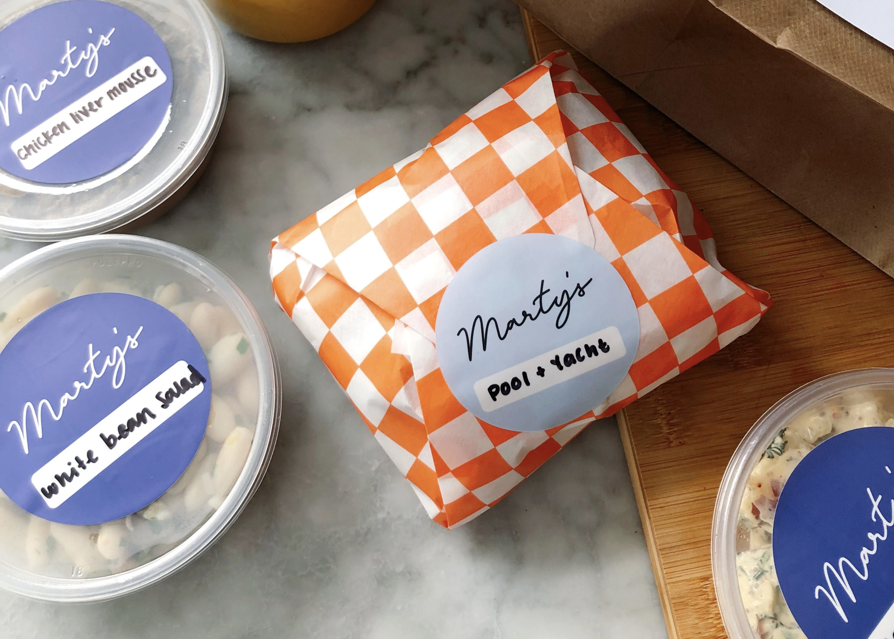 A sandwich wrapped in white and red checked wax paper with a Marty's sticker on it is flanked by deli containers of macaroni salad