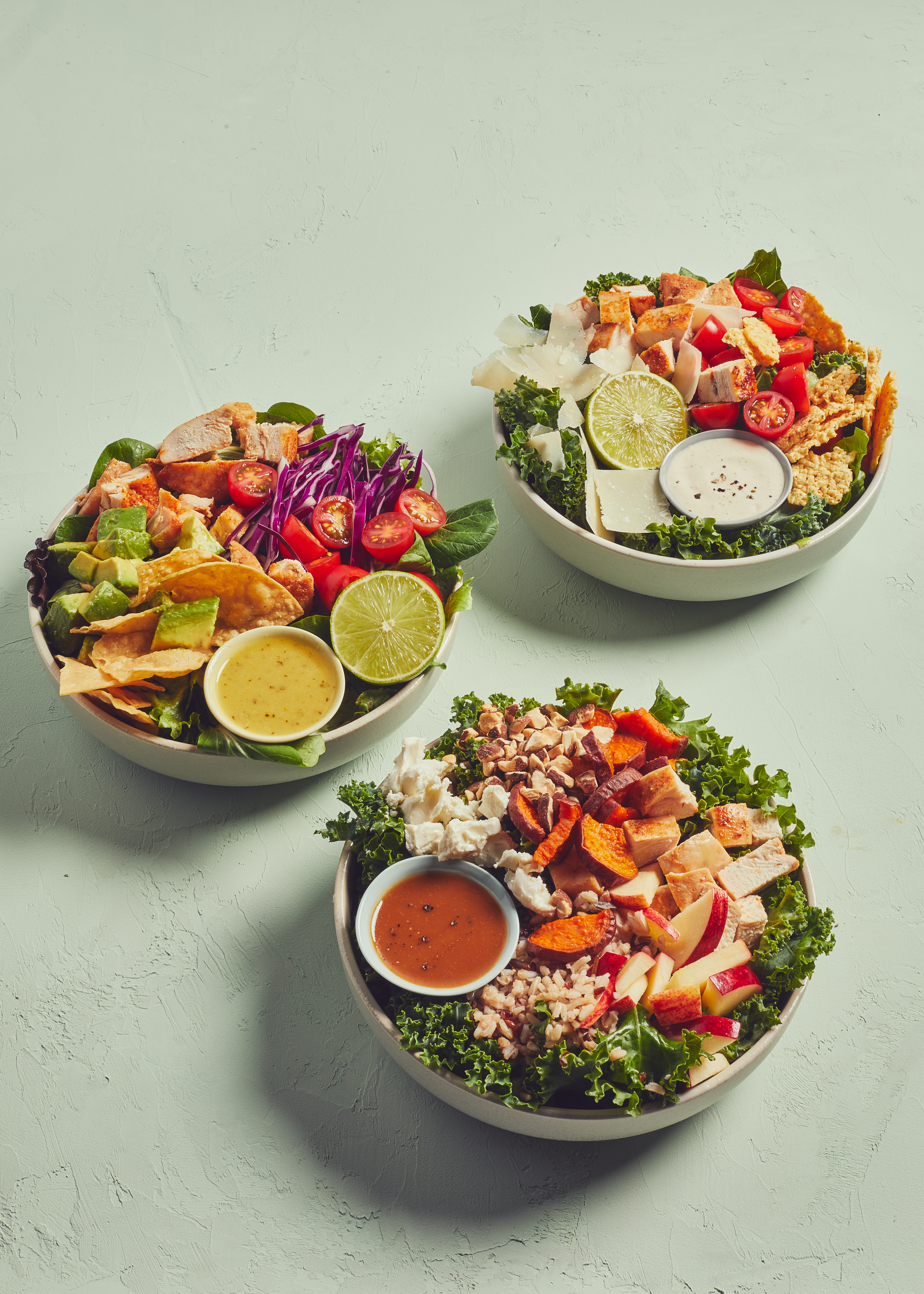 A trio of salads from Sweetgreen served in white bowls