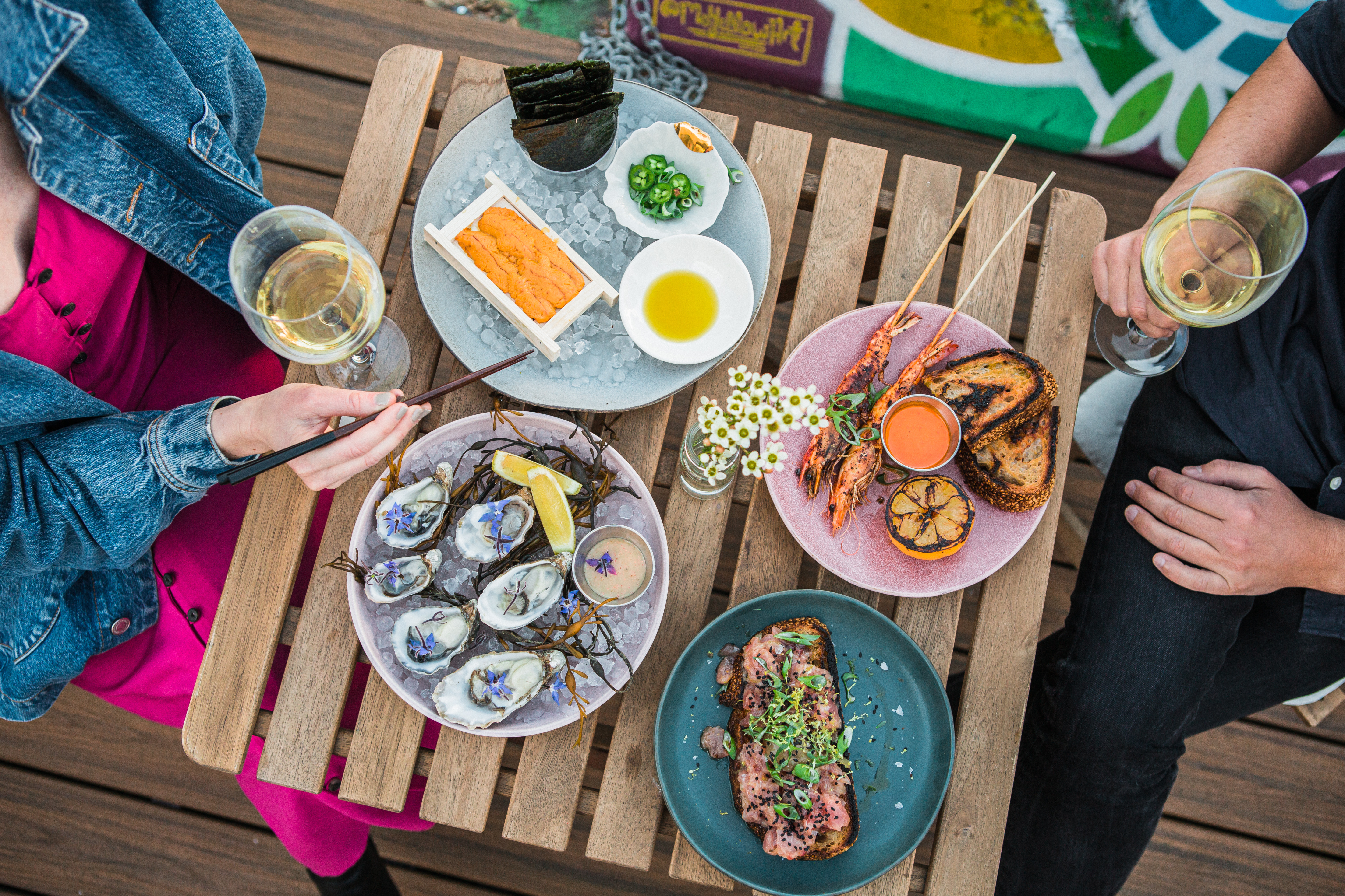 Two people shown from overhead with plates of seafood and grilled fish at Crudo e Nudo.