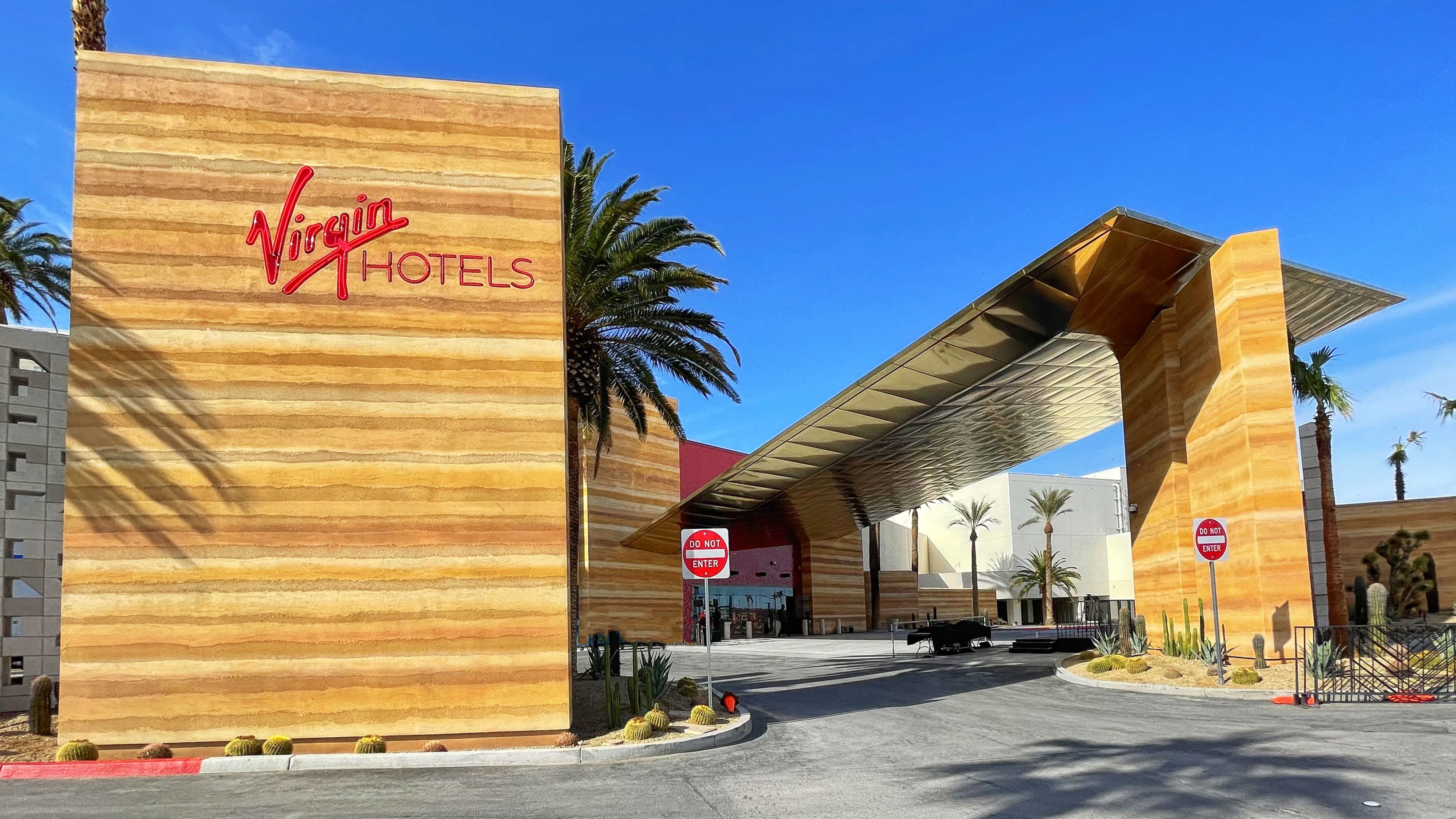 The exterior of a hotel with light woods and a palm tree