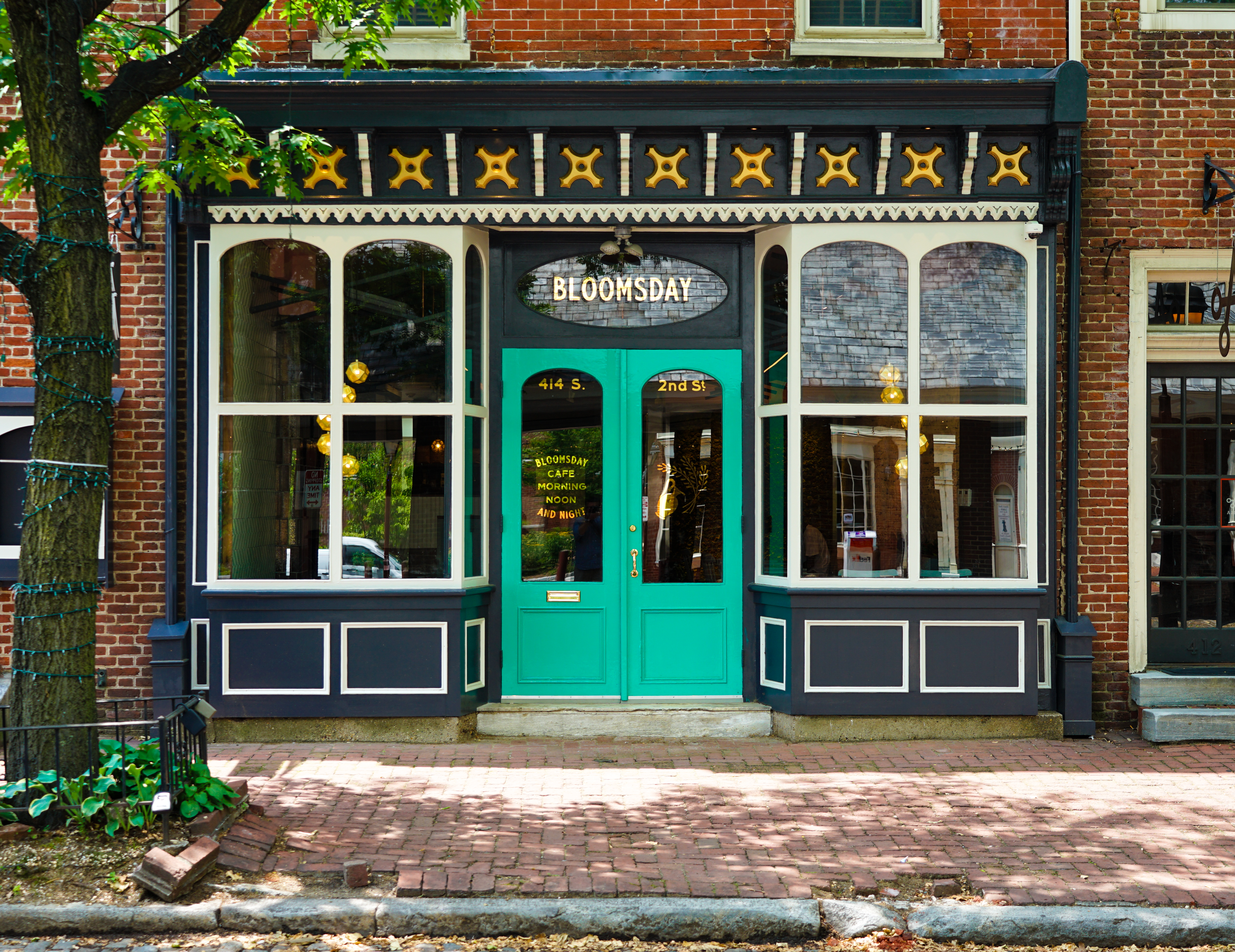 Bloomsday cafe front windows with a teal green door and a yellow and white overhang