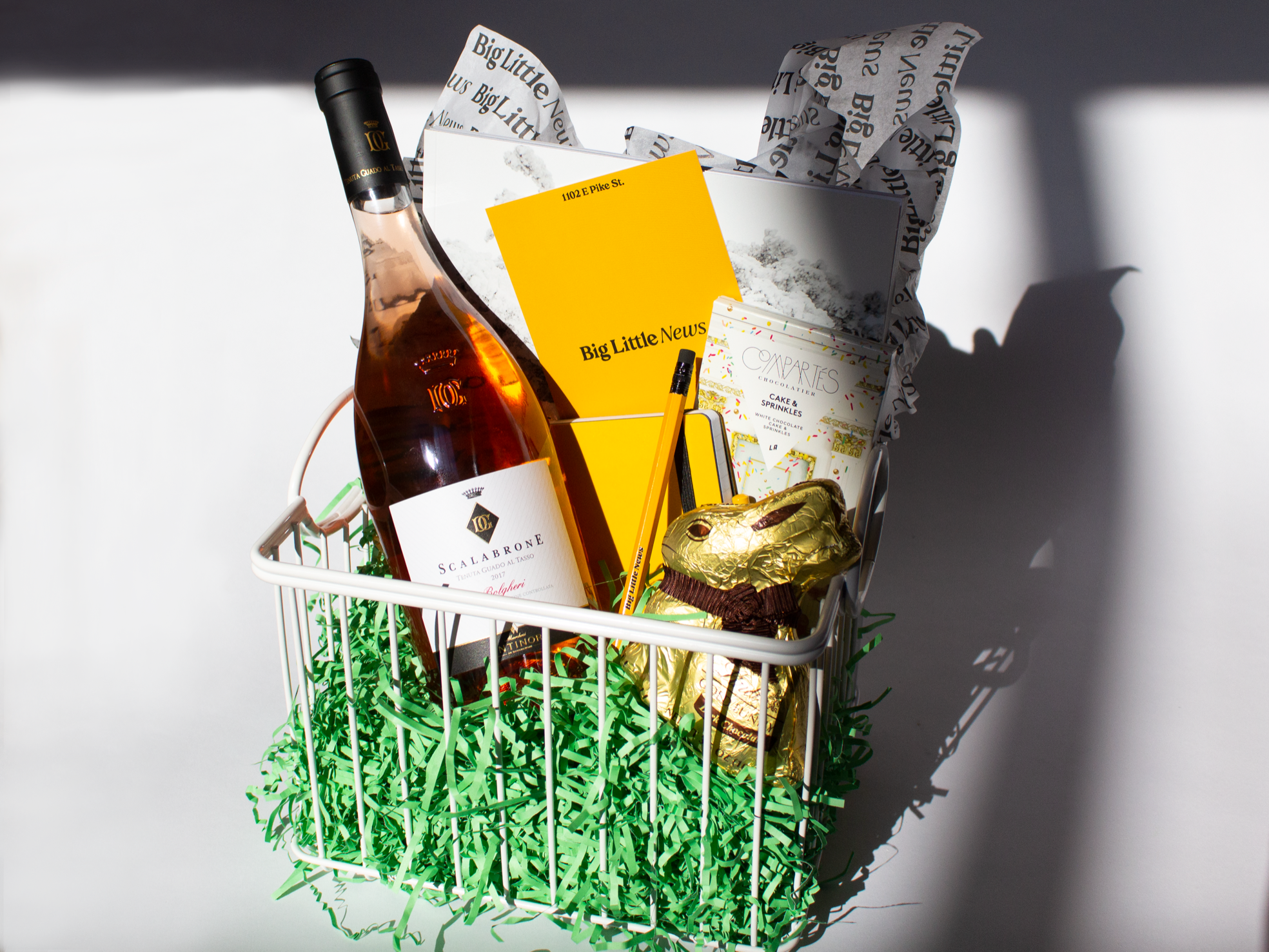 An Easter basket from Little Big News with rosé, a yellow notebook, pencil, chocolate bunny, candy bar, and fake green grass